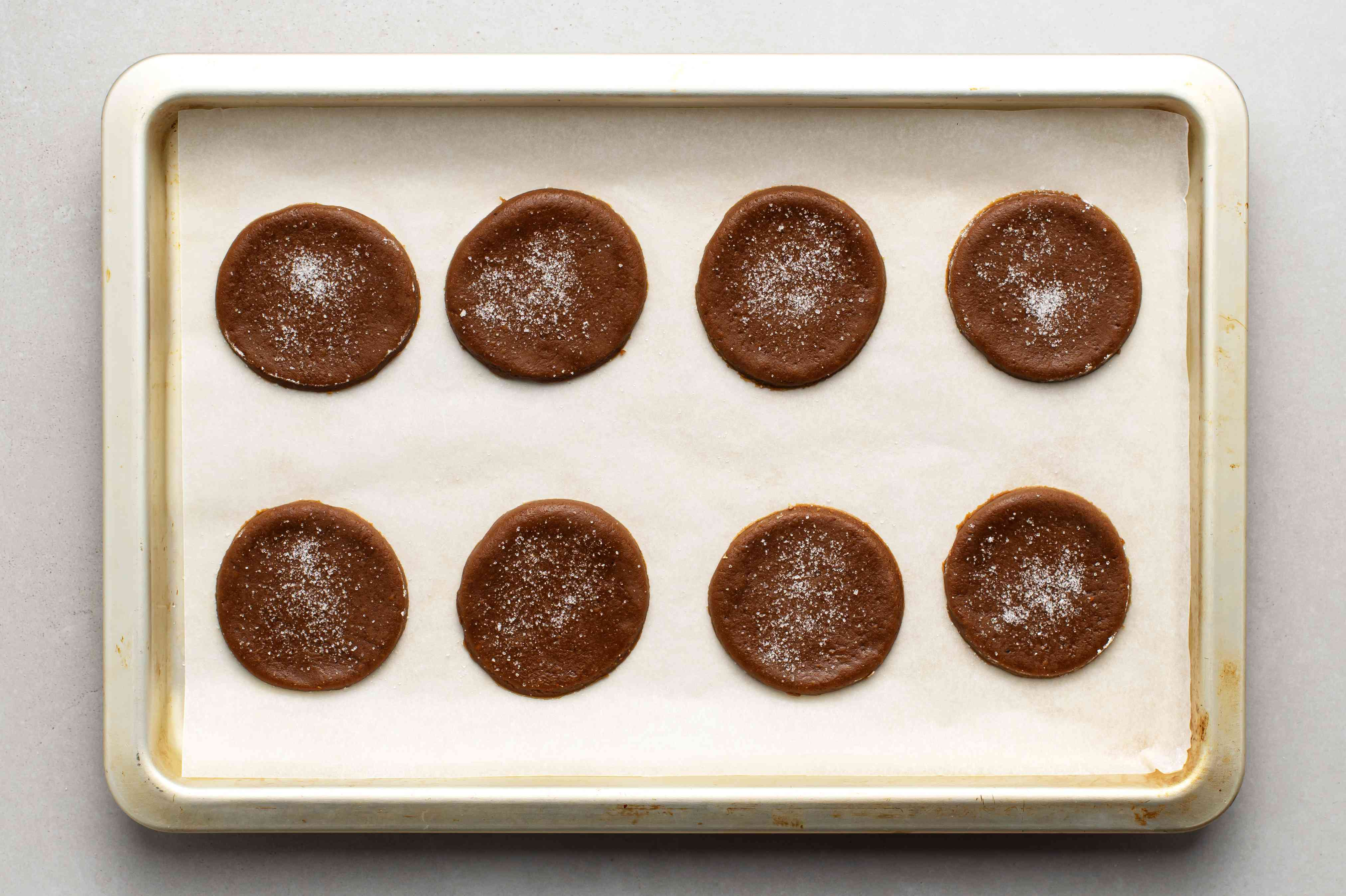 molasses cookies on a parchment paper lined baking sheet