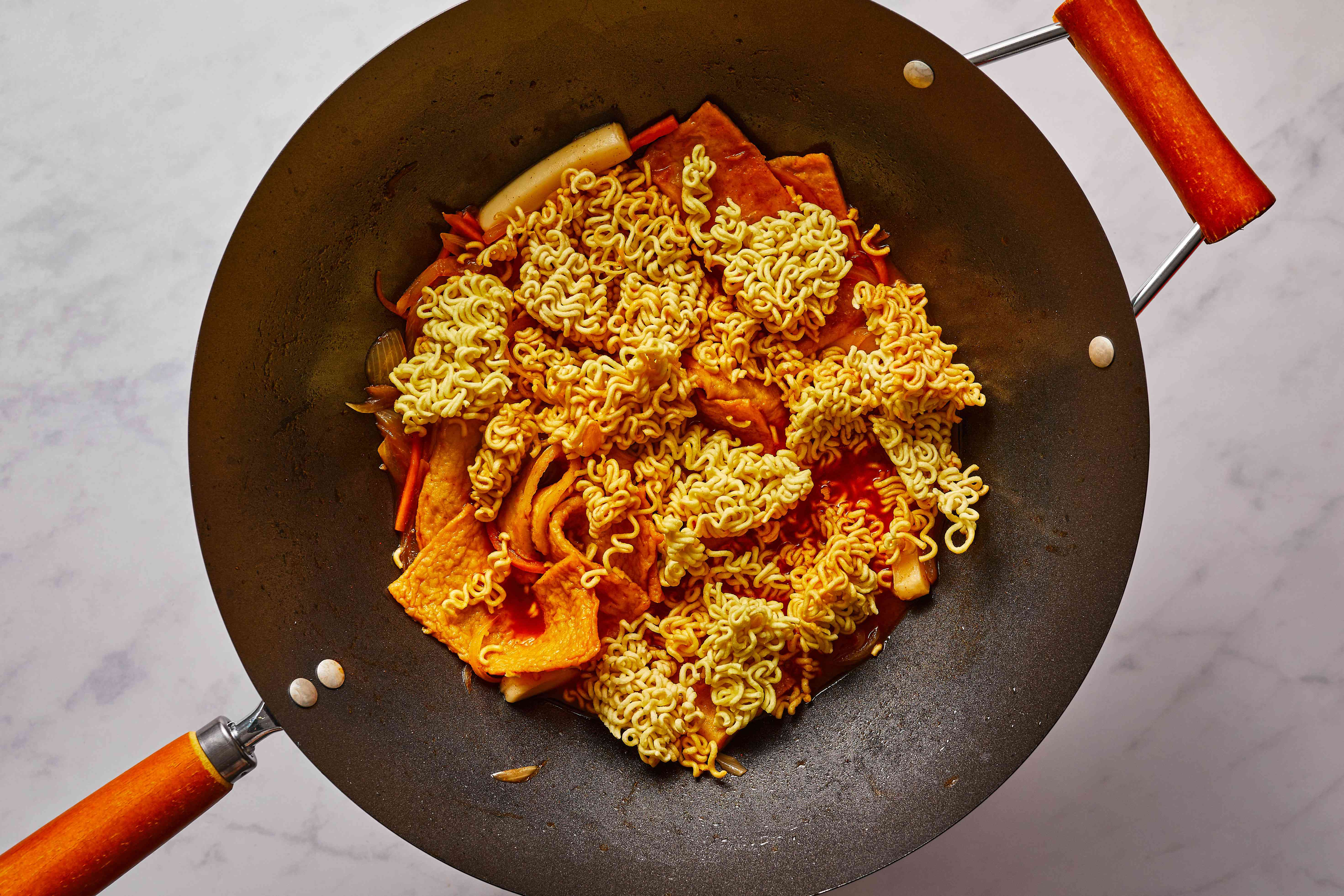 ramen added to the mixture in the pan