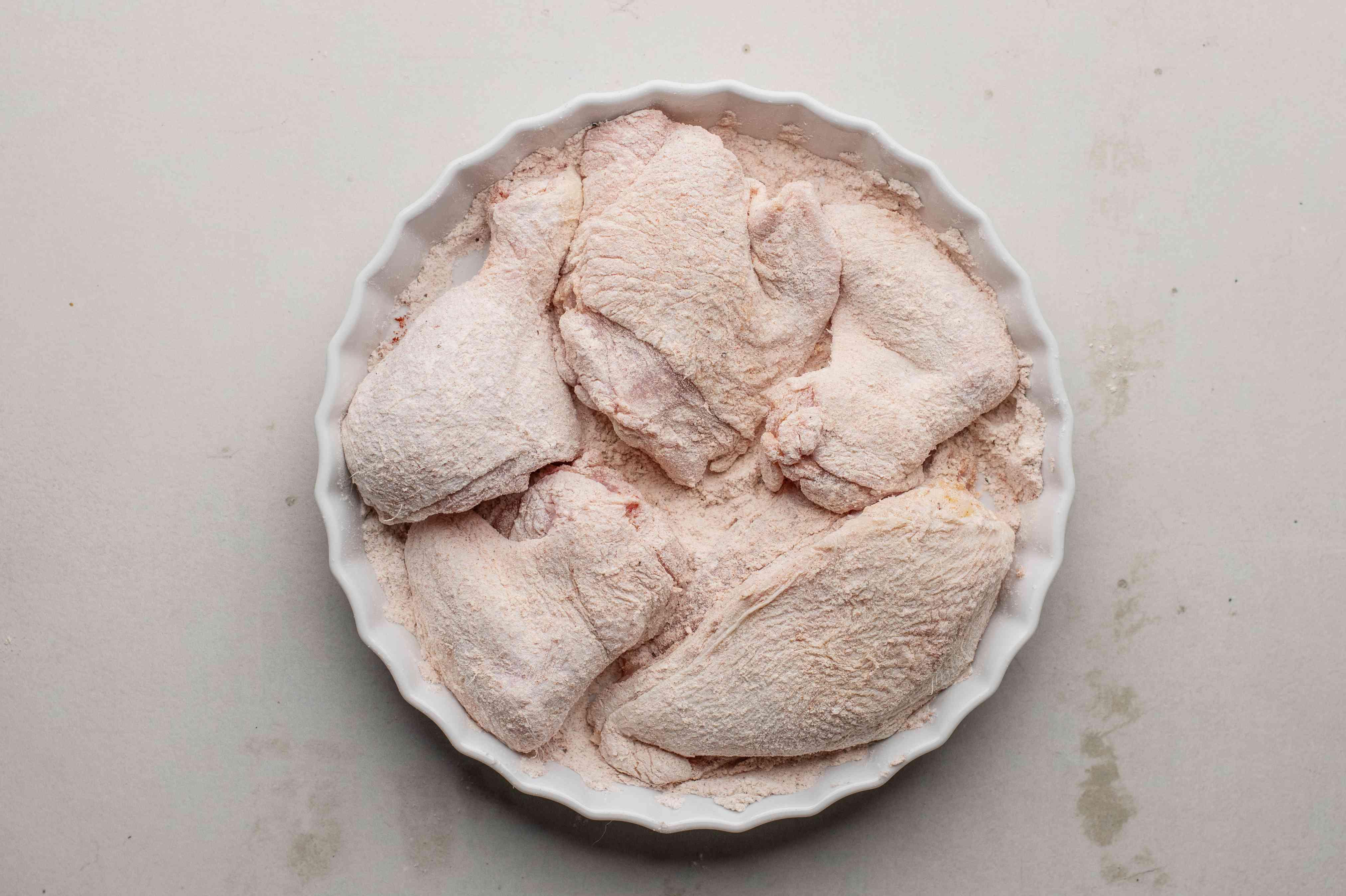 Coating chicken pieces in seasoned flour