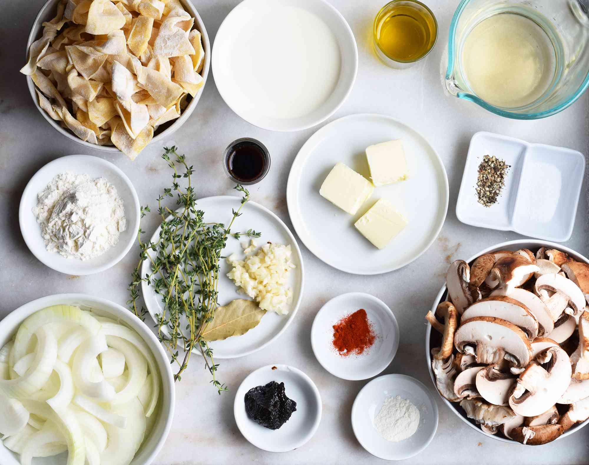 ingredients for mushroom stroganoff displayed on marble board