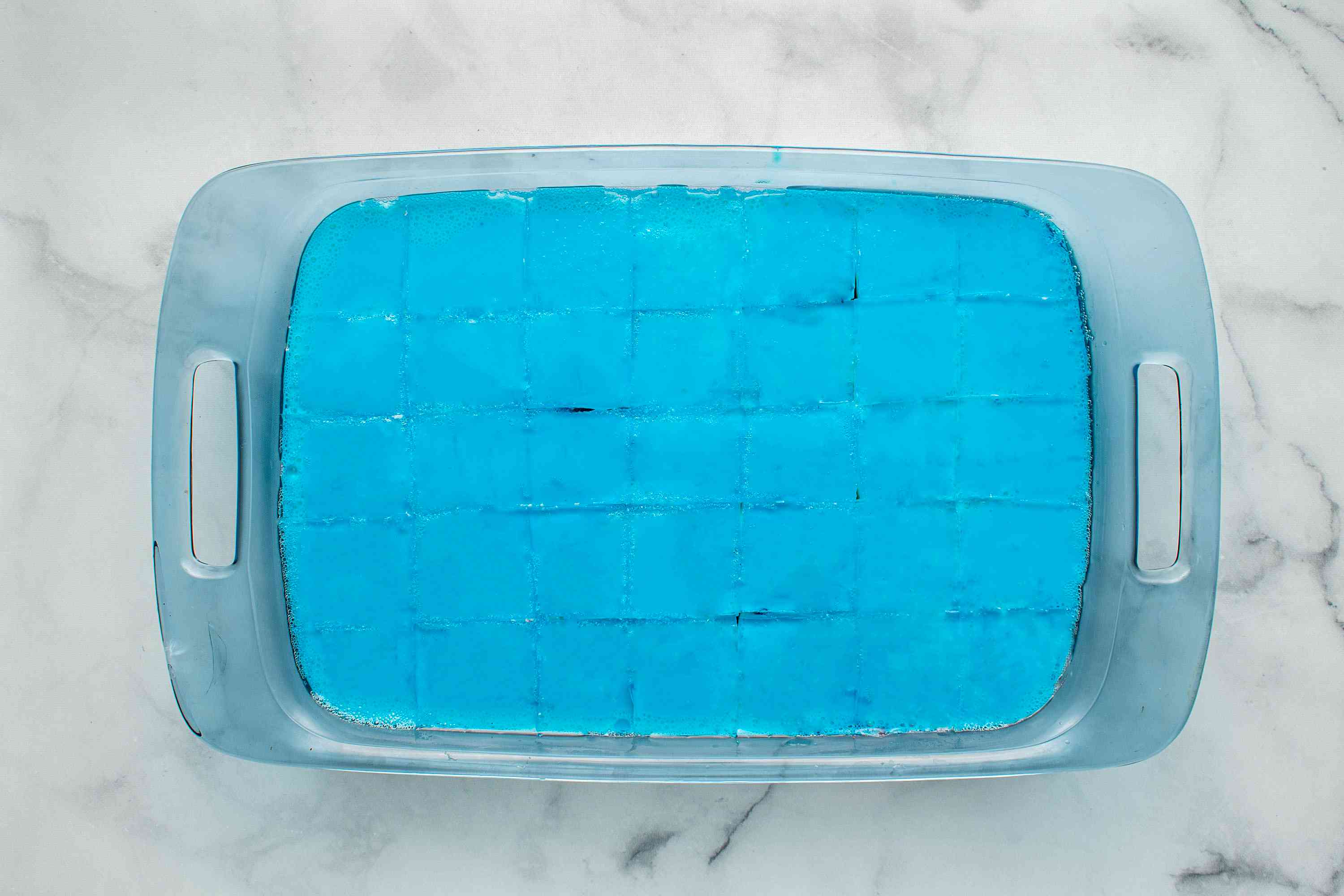 red, white and blue jello sliced into pieces in a dish