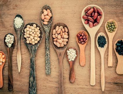 Various beans in wooden spoons