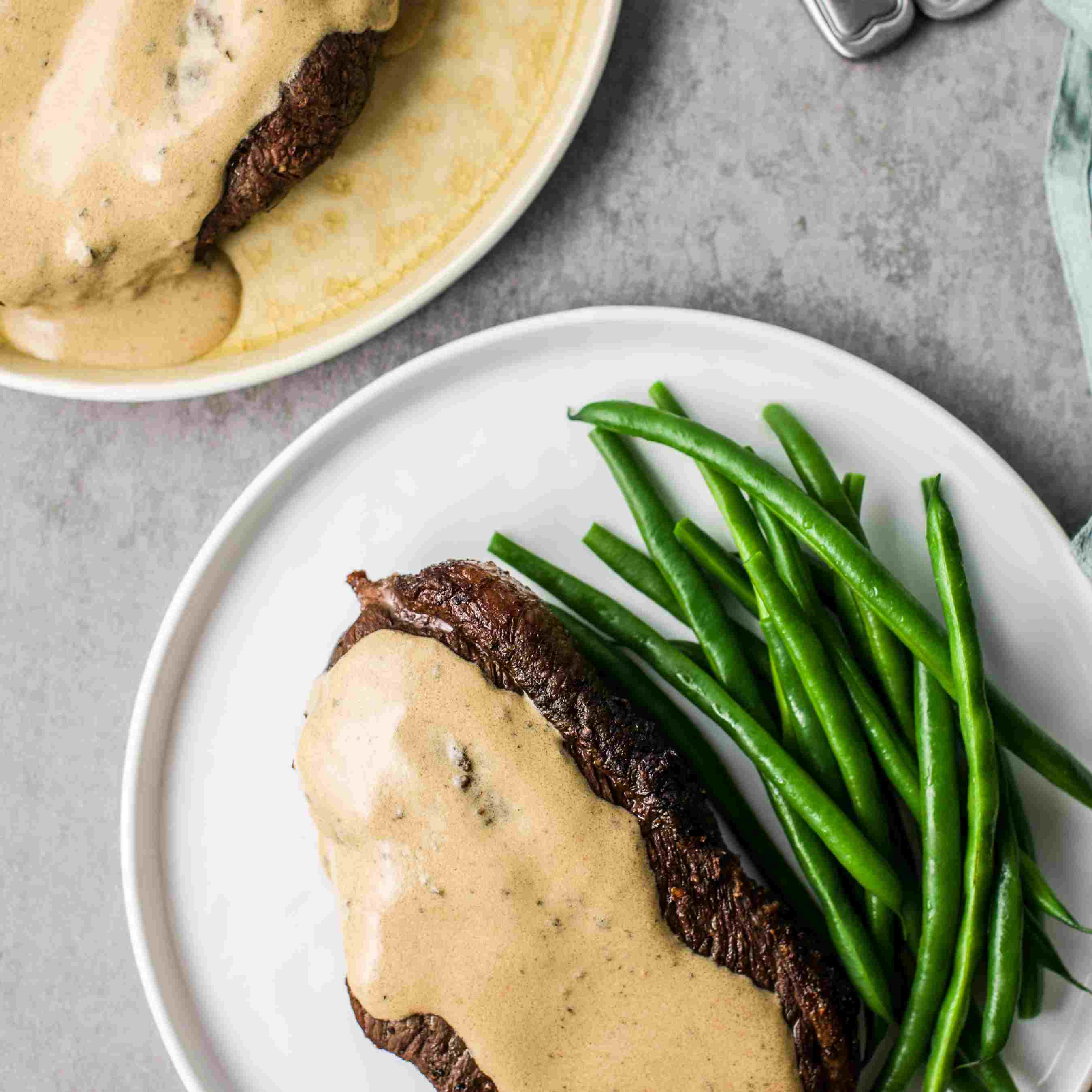Steak au Poivre on plates with green beans