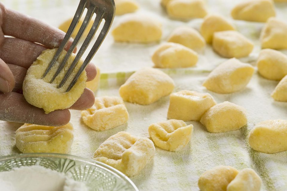 Gnocchi being pressed with fork