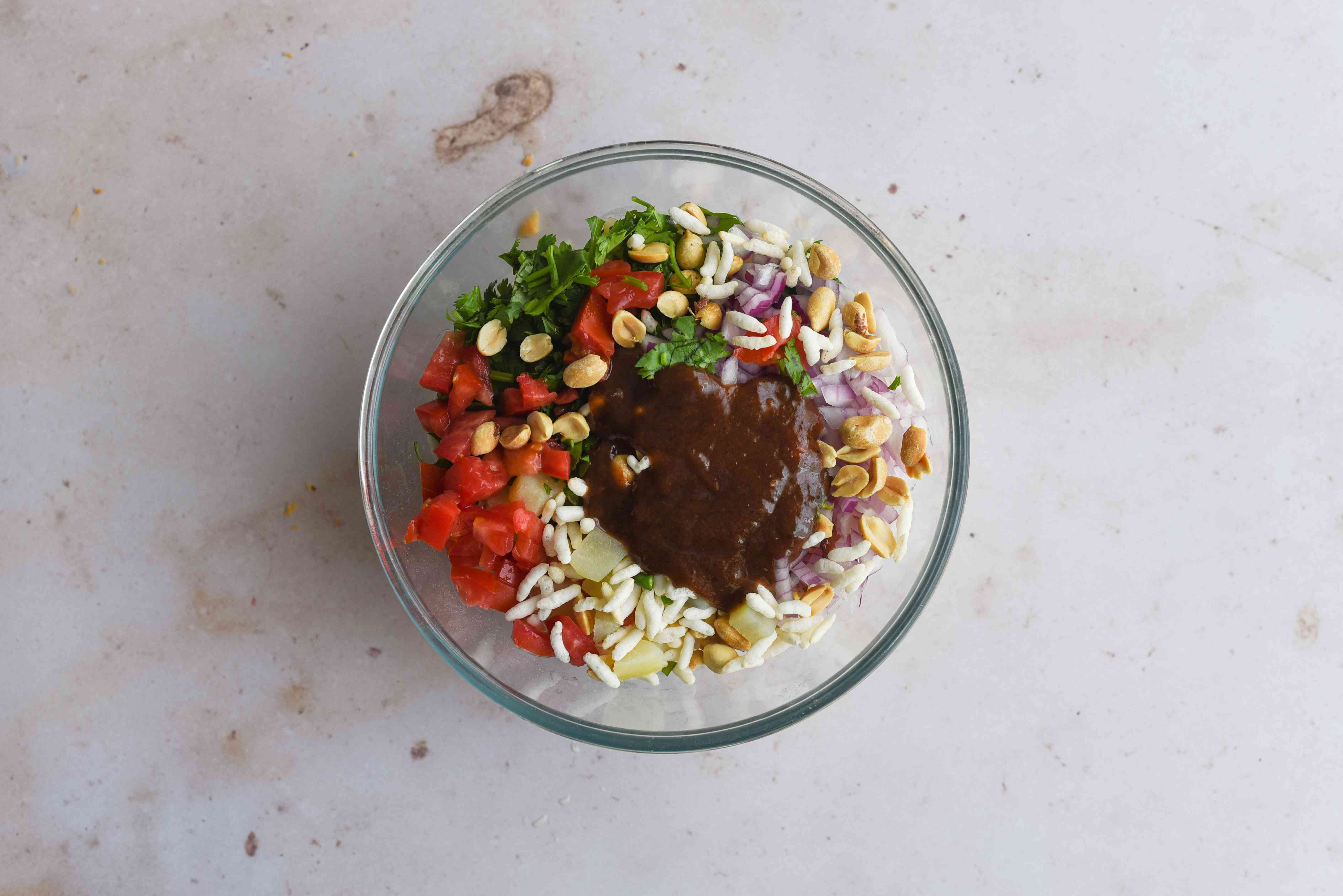Add the tamarind chutney or mint-coriander chutney to the ingredients in the bowl