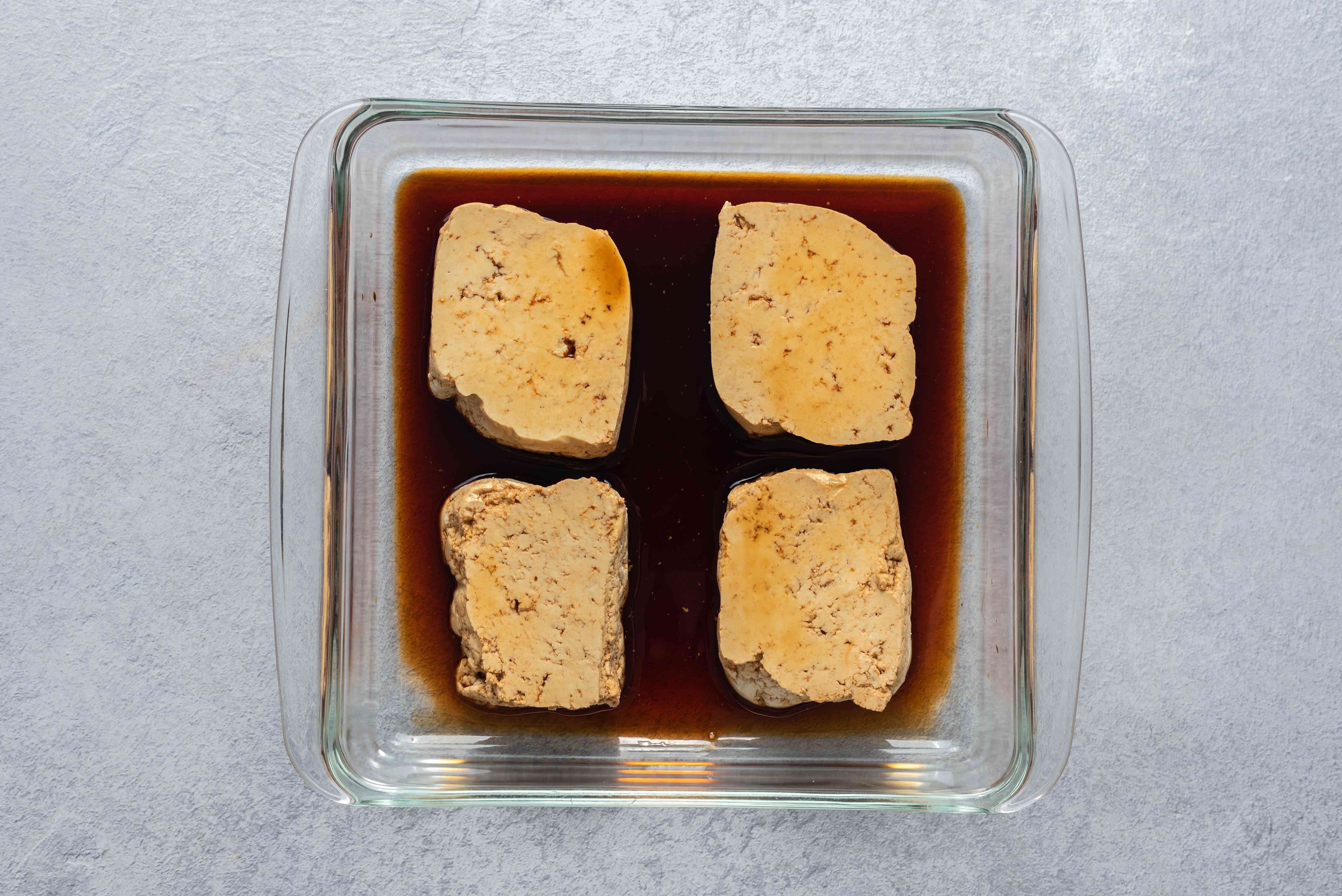 Tofu in a shallow dish with soy sauce