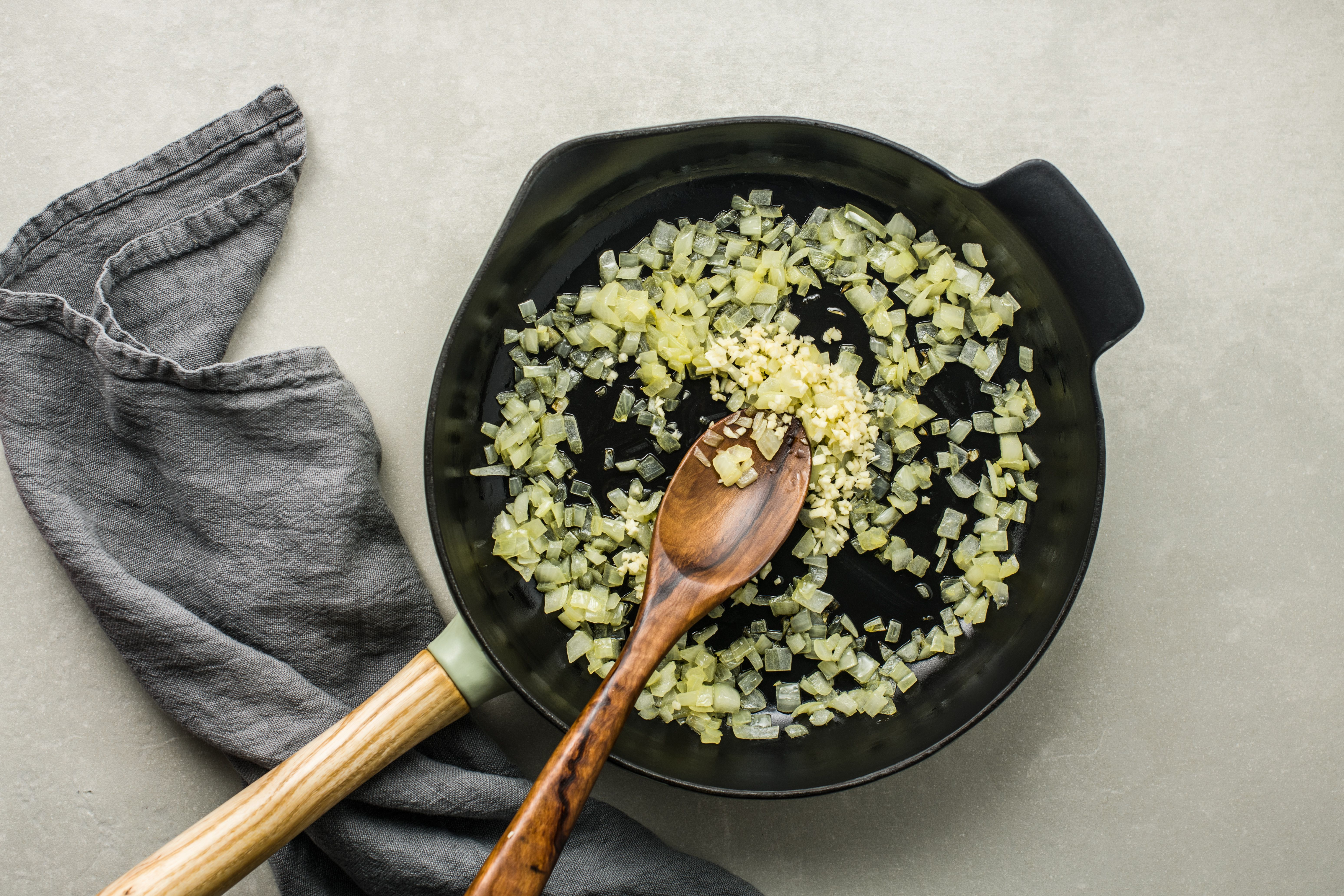 Wooden spoon sauteing onions in skillet