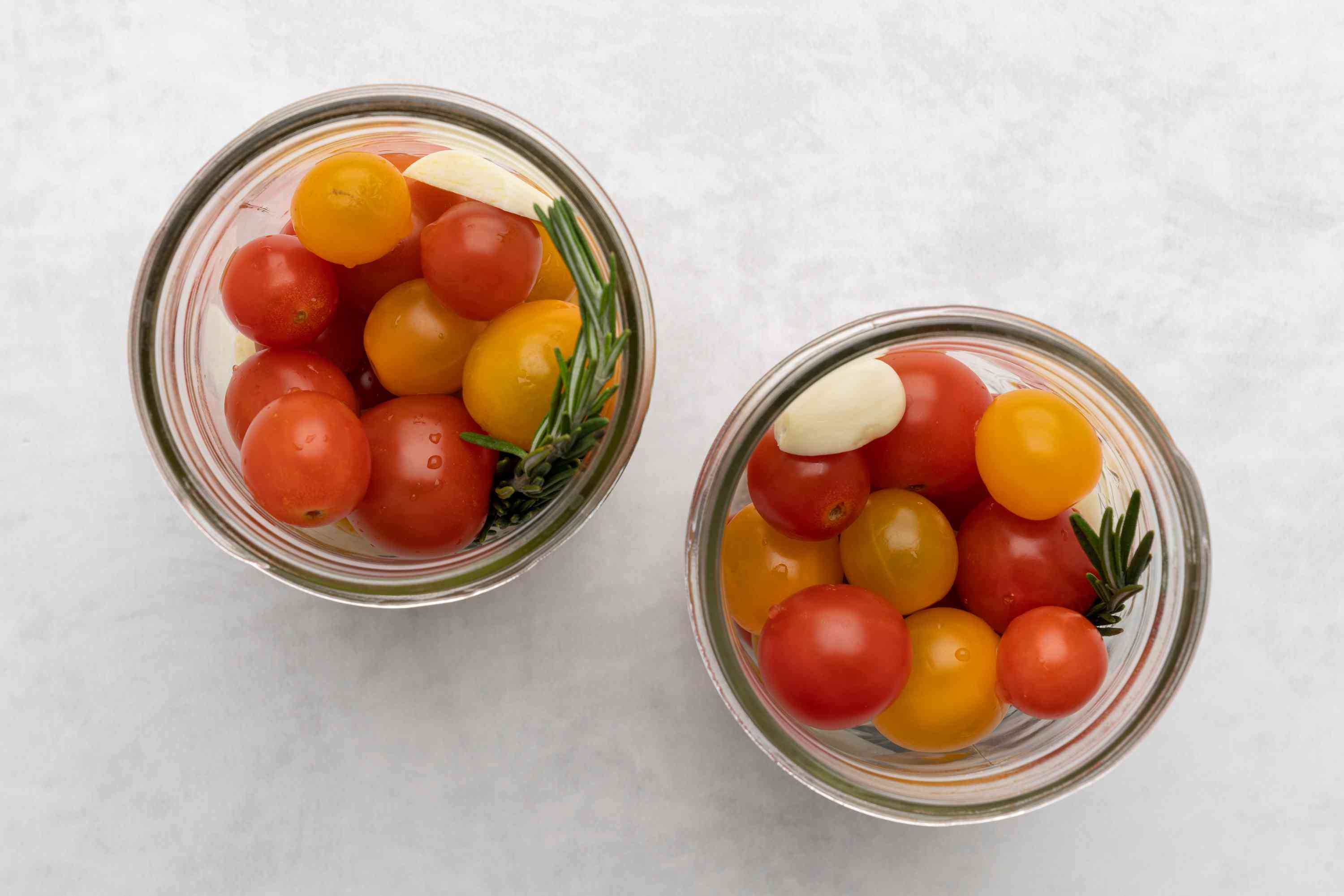 Cherry Tomatoes, garlic, and rosemary in two jars