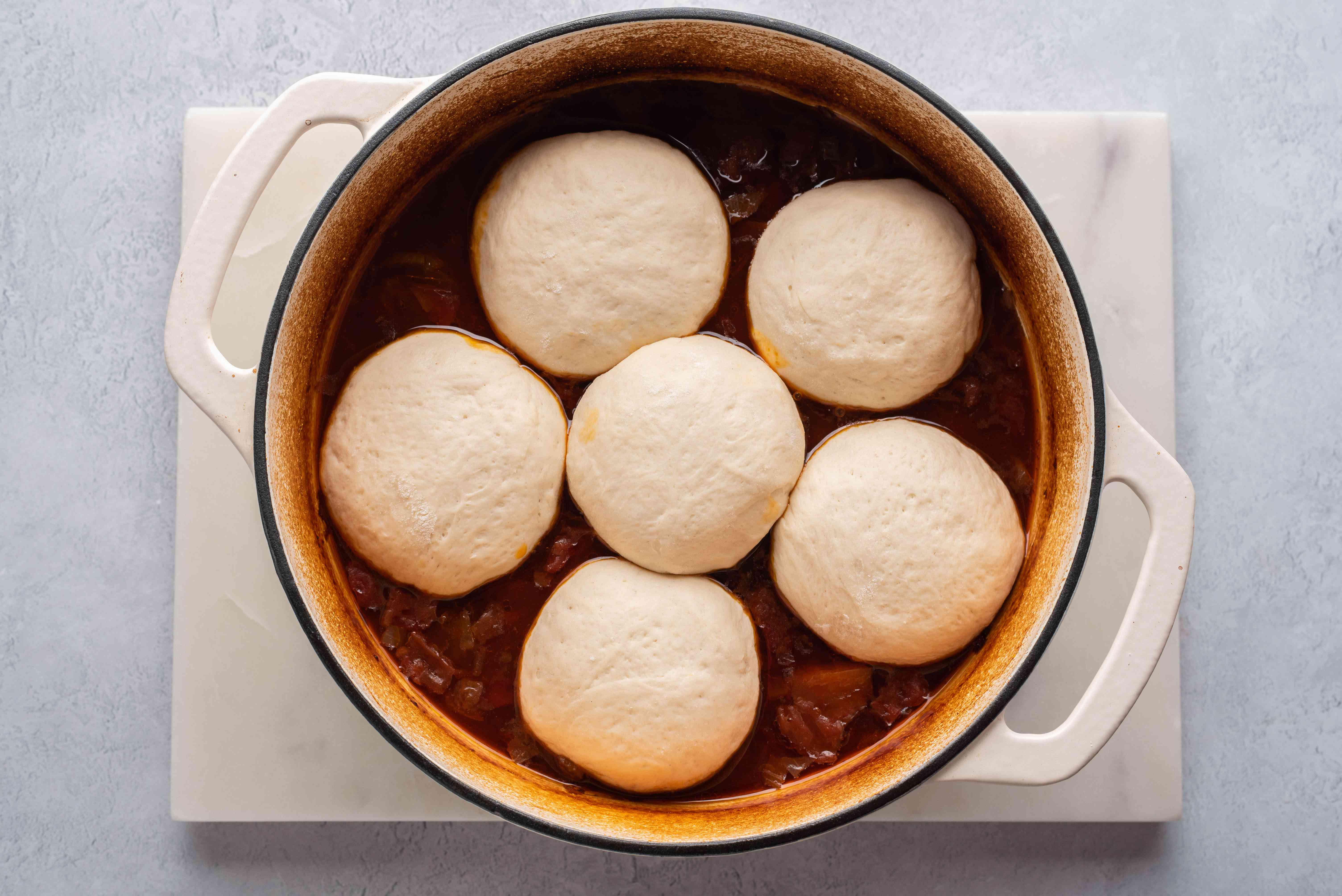 place the dough balls on top of a stew in a pot