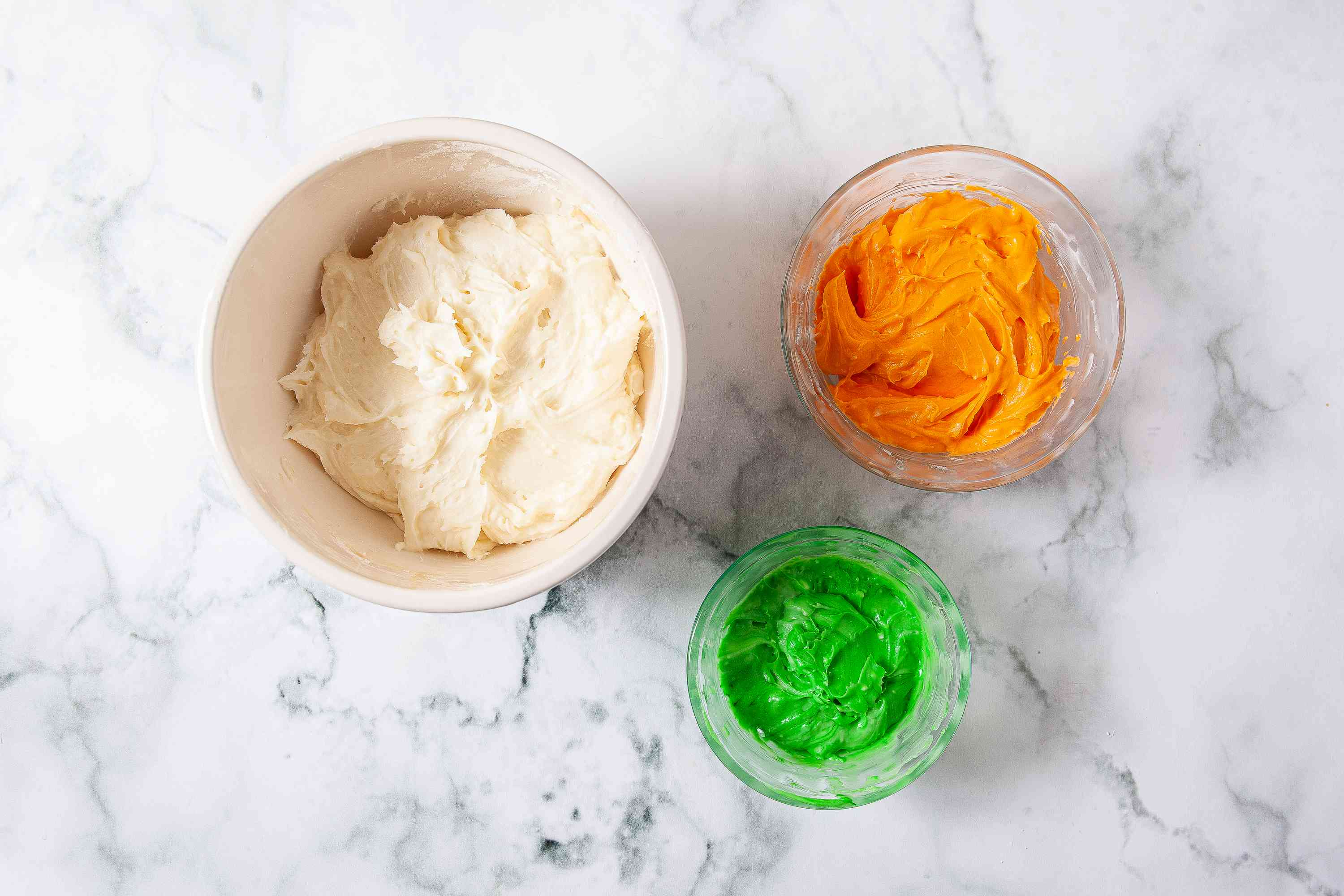 Frosting divided into three bowls with one green and one orange
