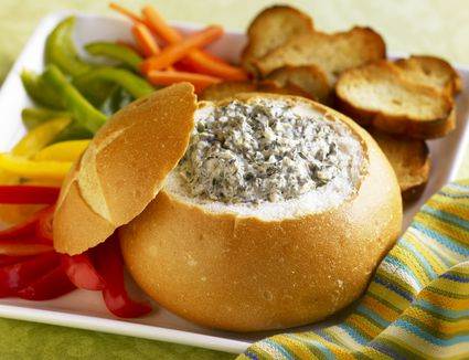 Spinach dip in bread bowl with veggies and bread
