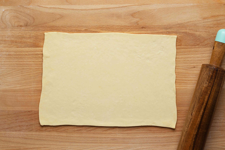 Rectangular sheet of dough on wooden cutting board