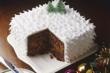 Christmas cake frosted in white to look like snow and adorned with tiny faux pine trees