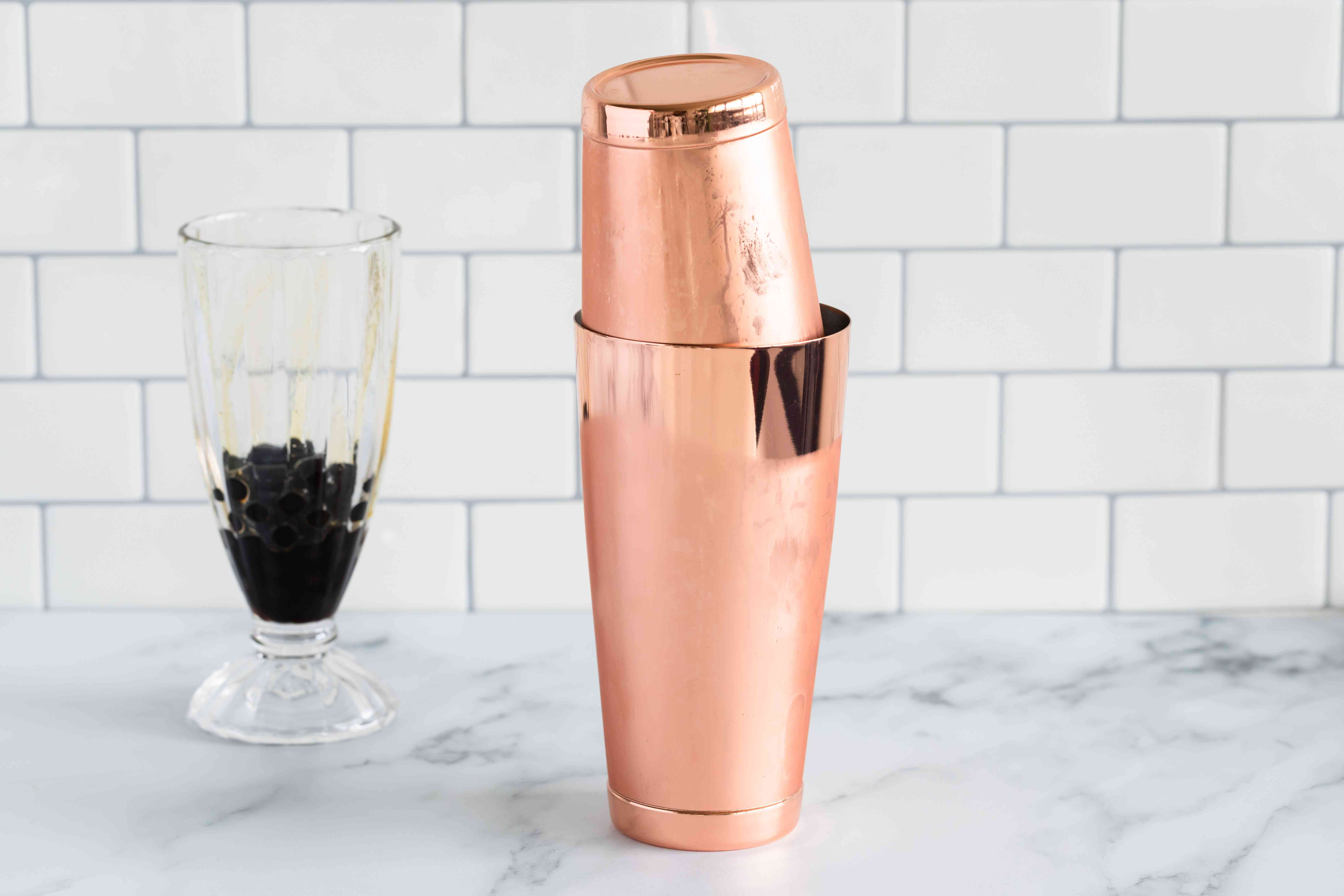 Combine milk and syrup in cocktail shaker