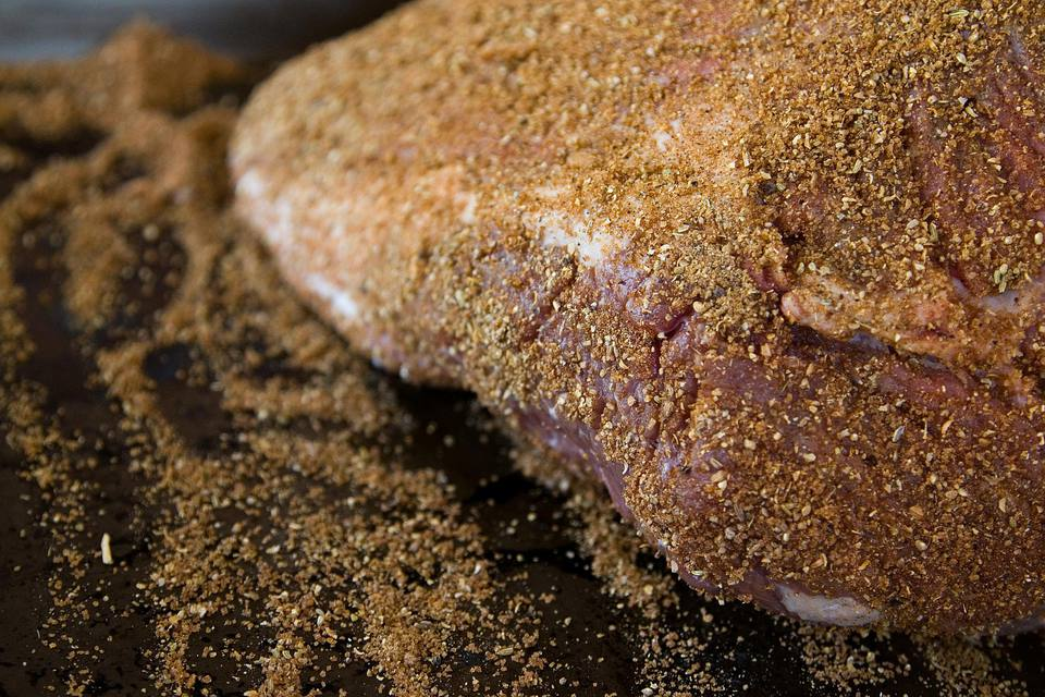 Rubbing spices onto brisket