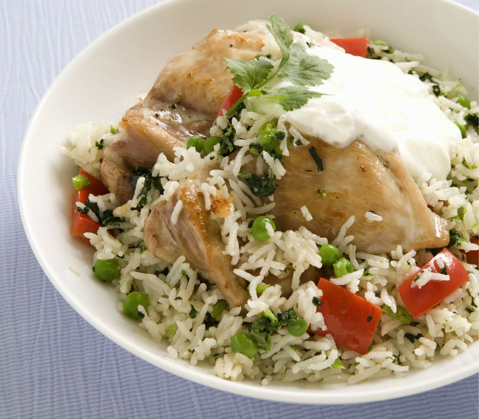 Pilau rice with chicken, spinach, peas and pepper in bowl,