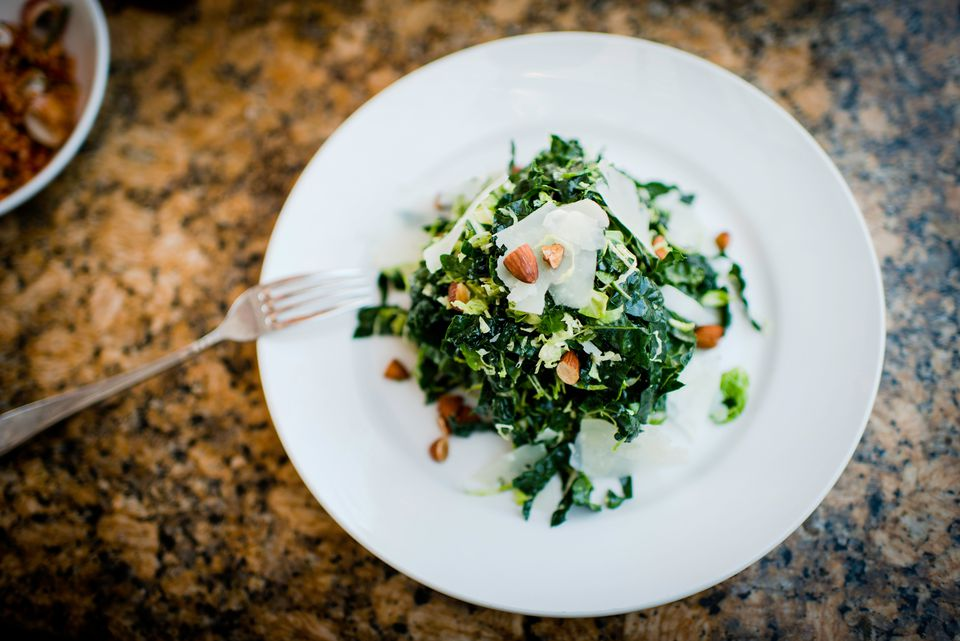Plate of kale salad and nuts on restaurant table
