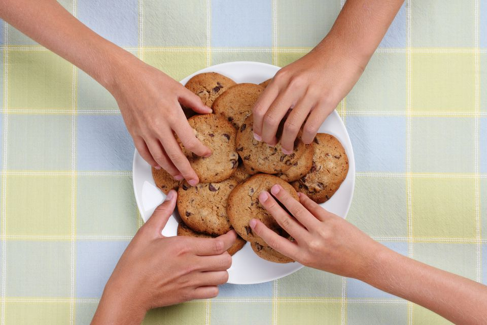 Hands grabbing for chocolate chip cookies on plate