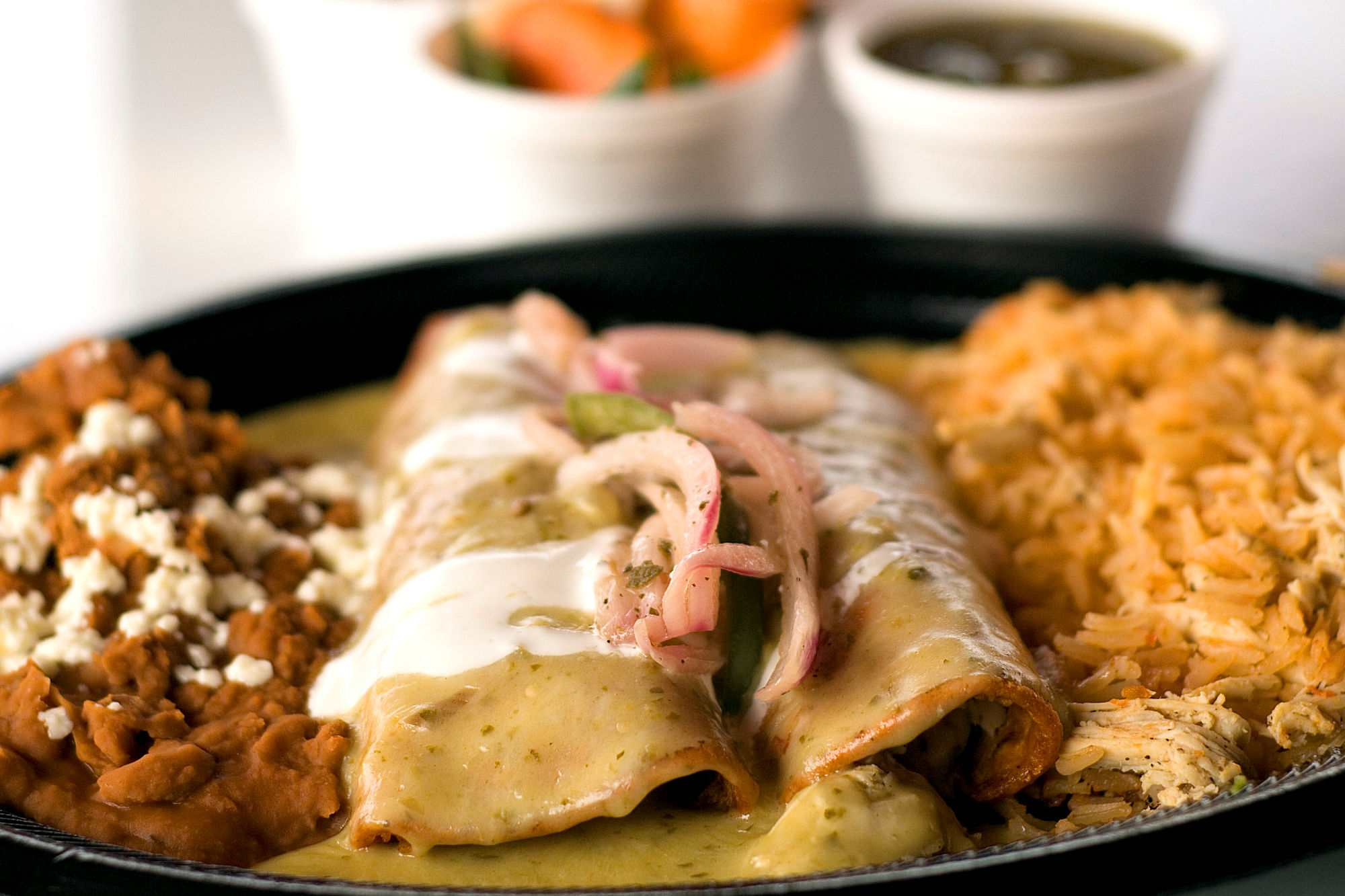 Enchiladas on plate with rice and beans.