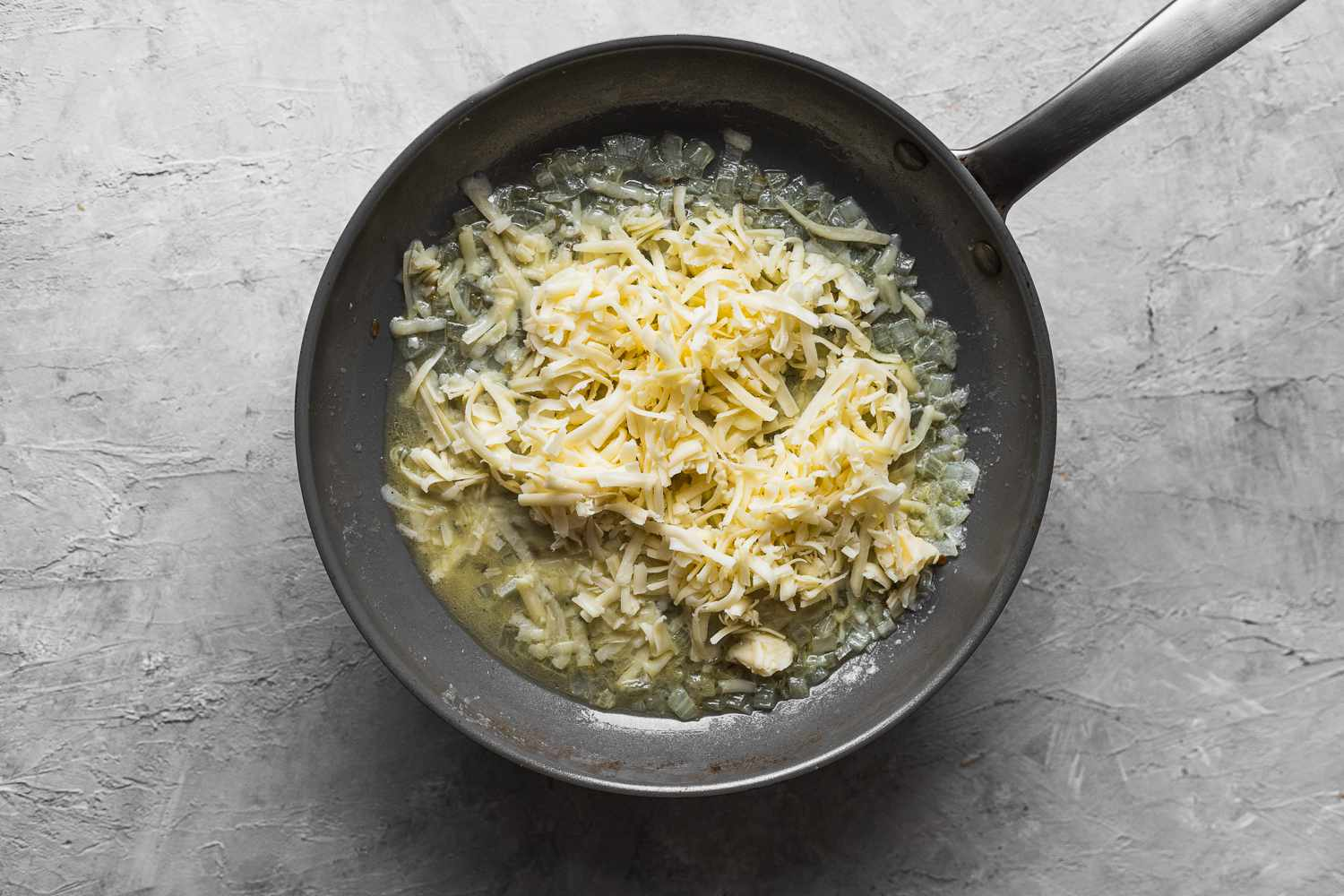 water and cheddar with onions in a pan