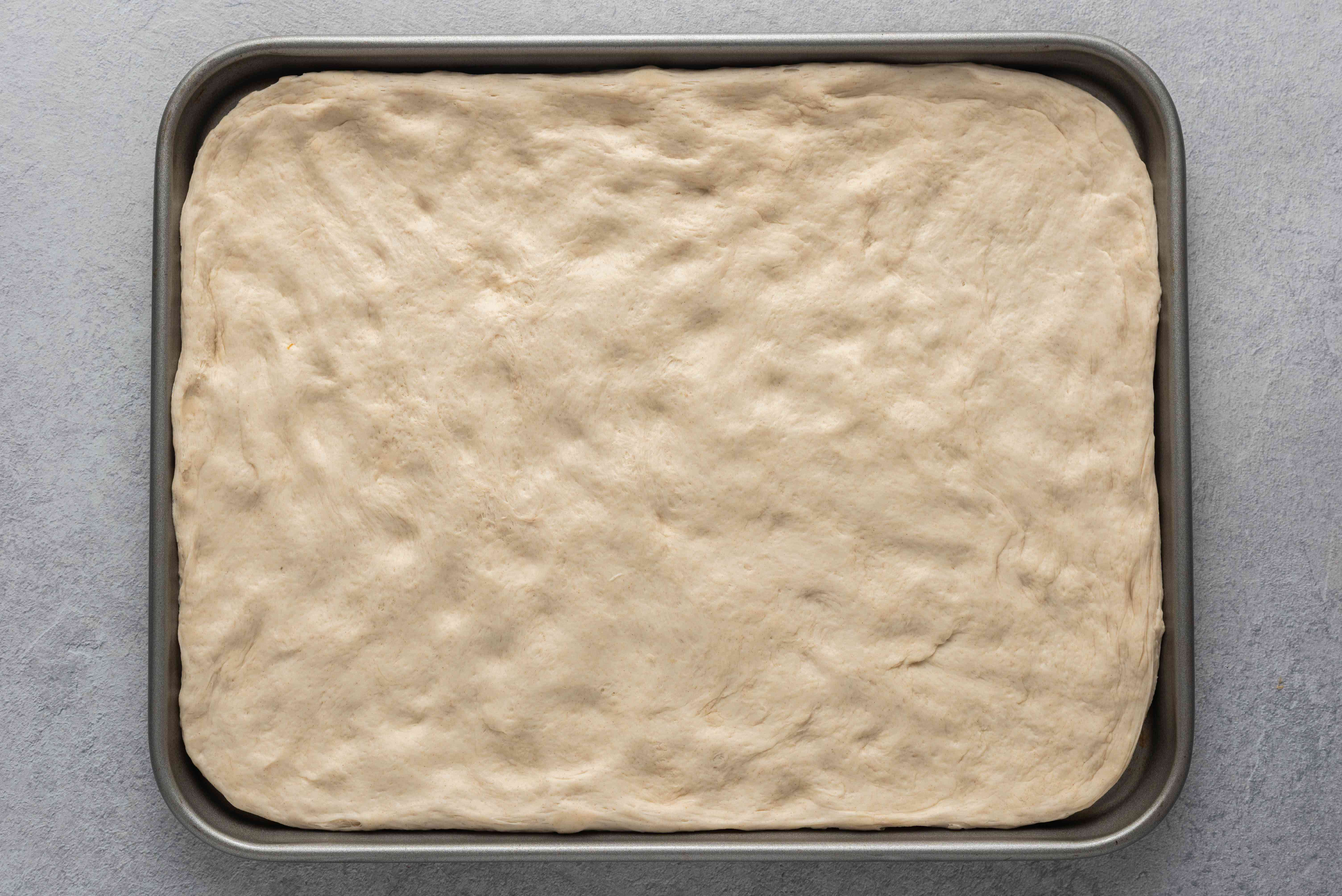 pizza dough on a baking sheet
