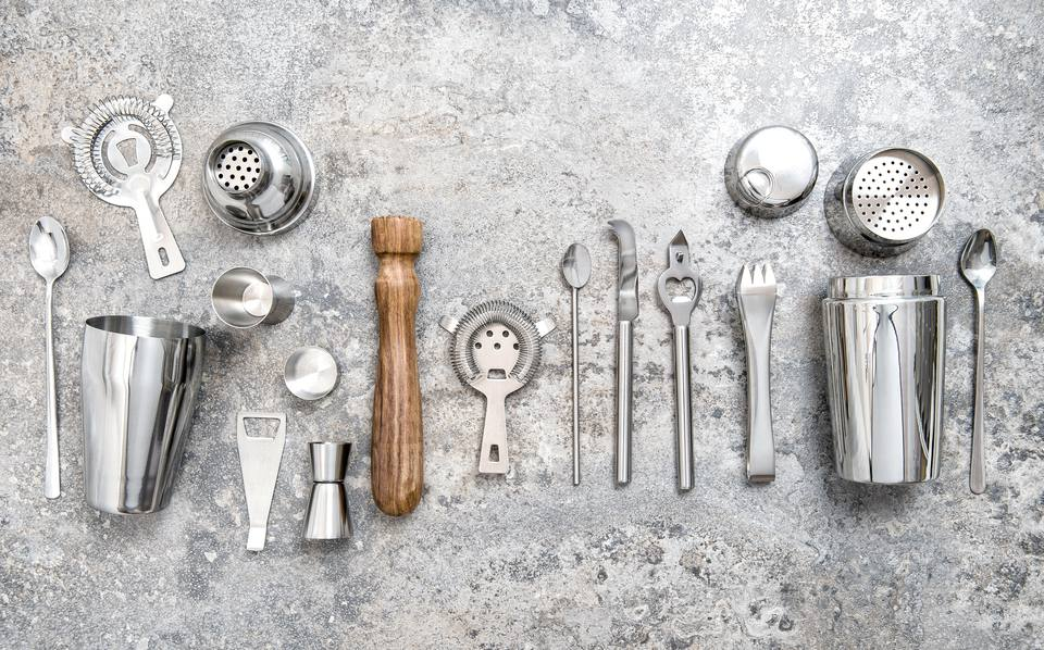 Collection of stainless steel bar tools and a wooden muddler on a cement backdrop.