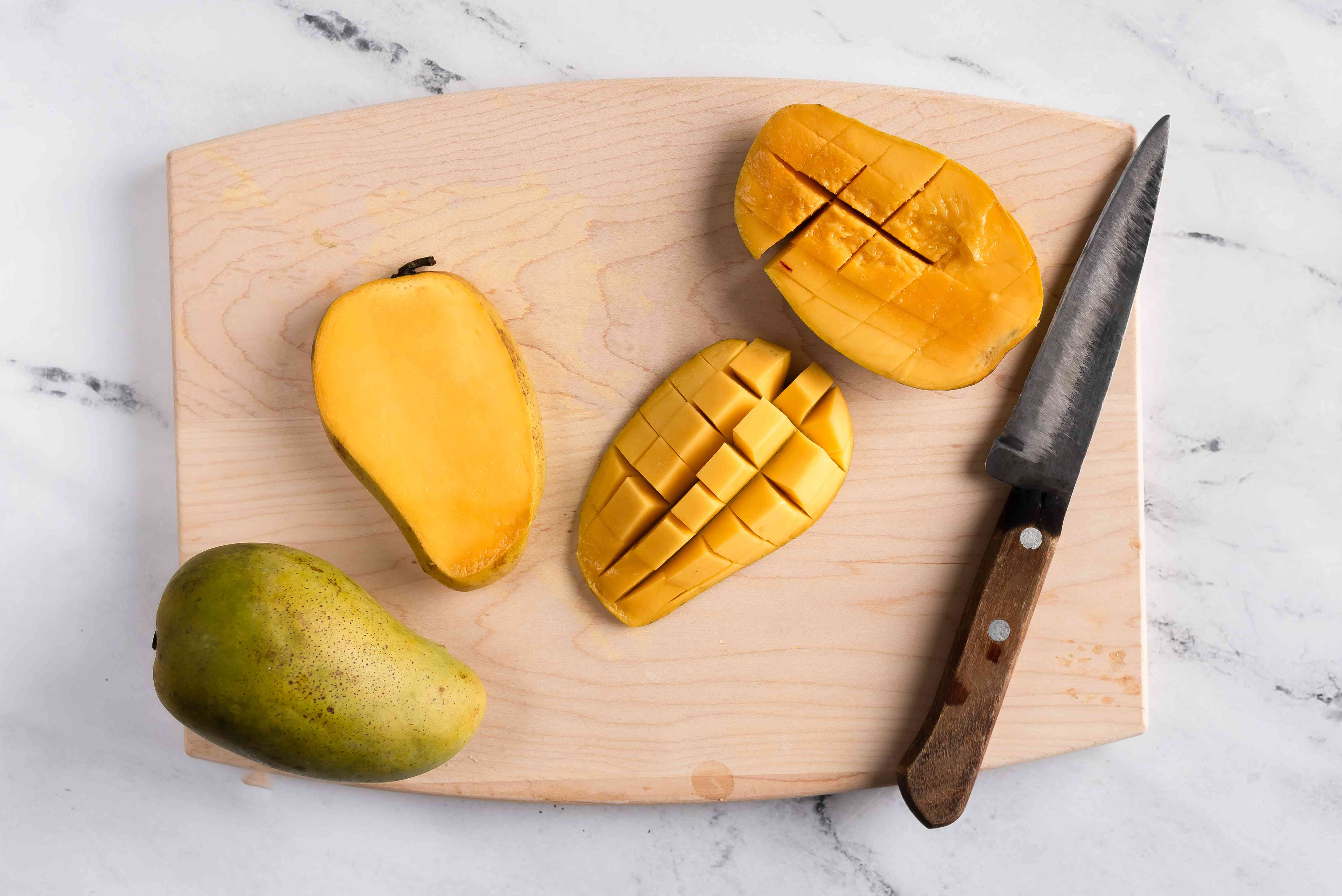 Mangoes scored with a sharp knife on a cutting board