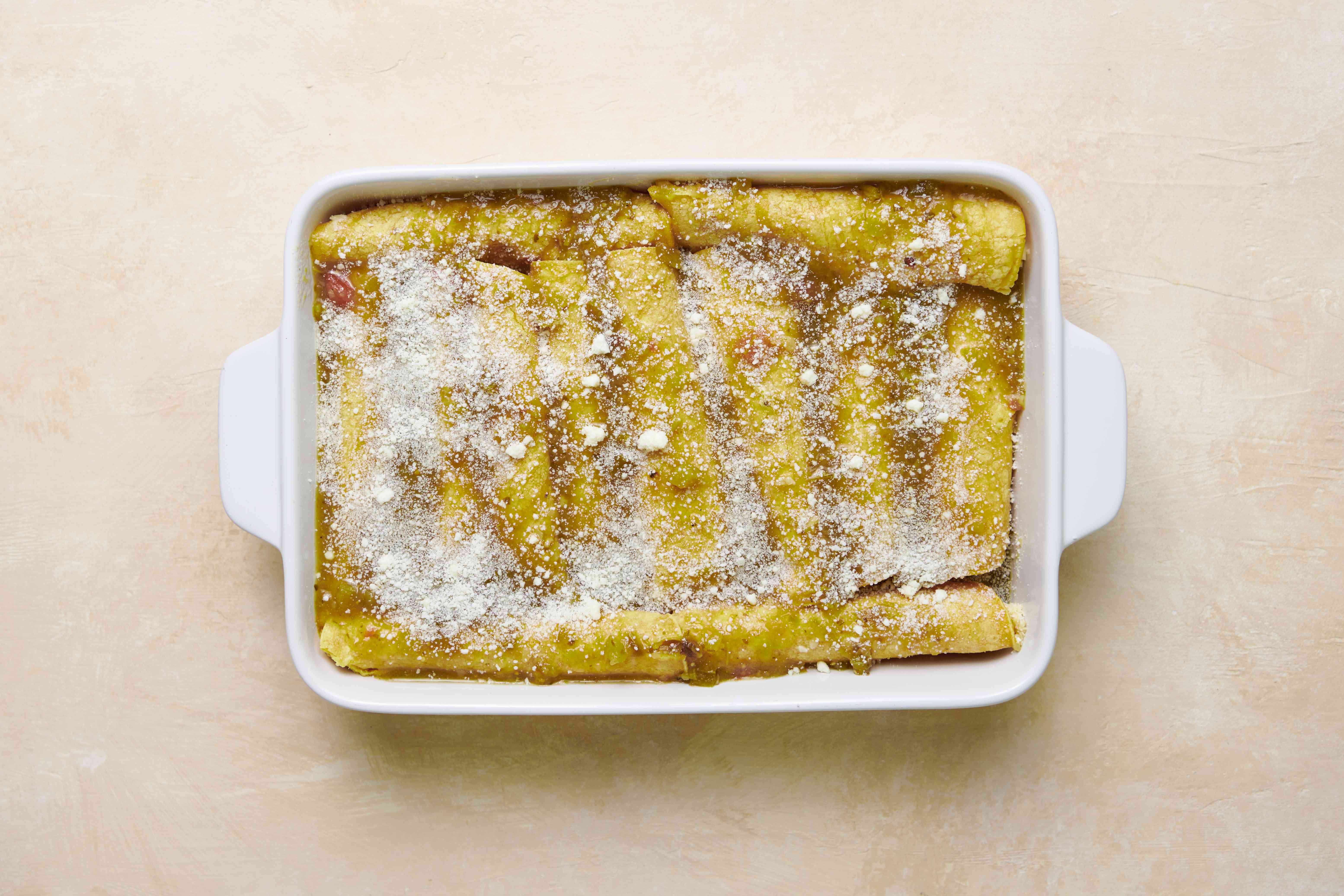 Enchiladas Verdes (Green Enchiladas) With Chicken in a baking dish with sauce and cotija on top