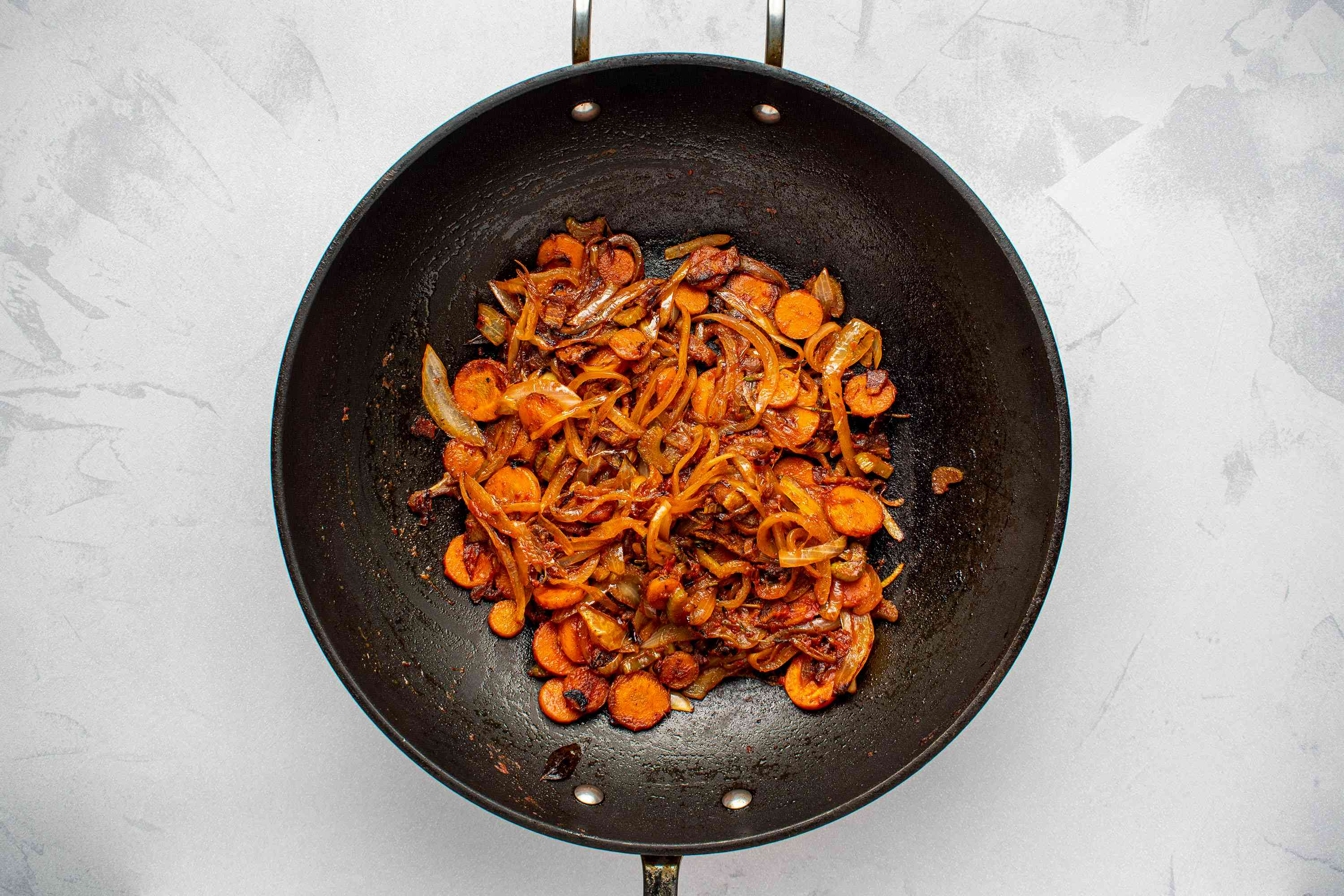 tomato paste added to the vegetable mixture in a wok