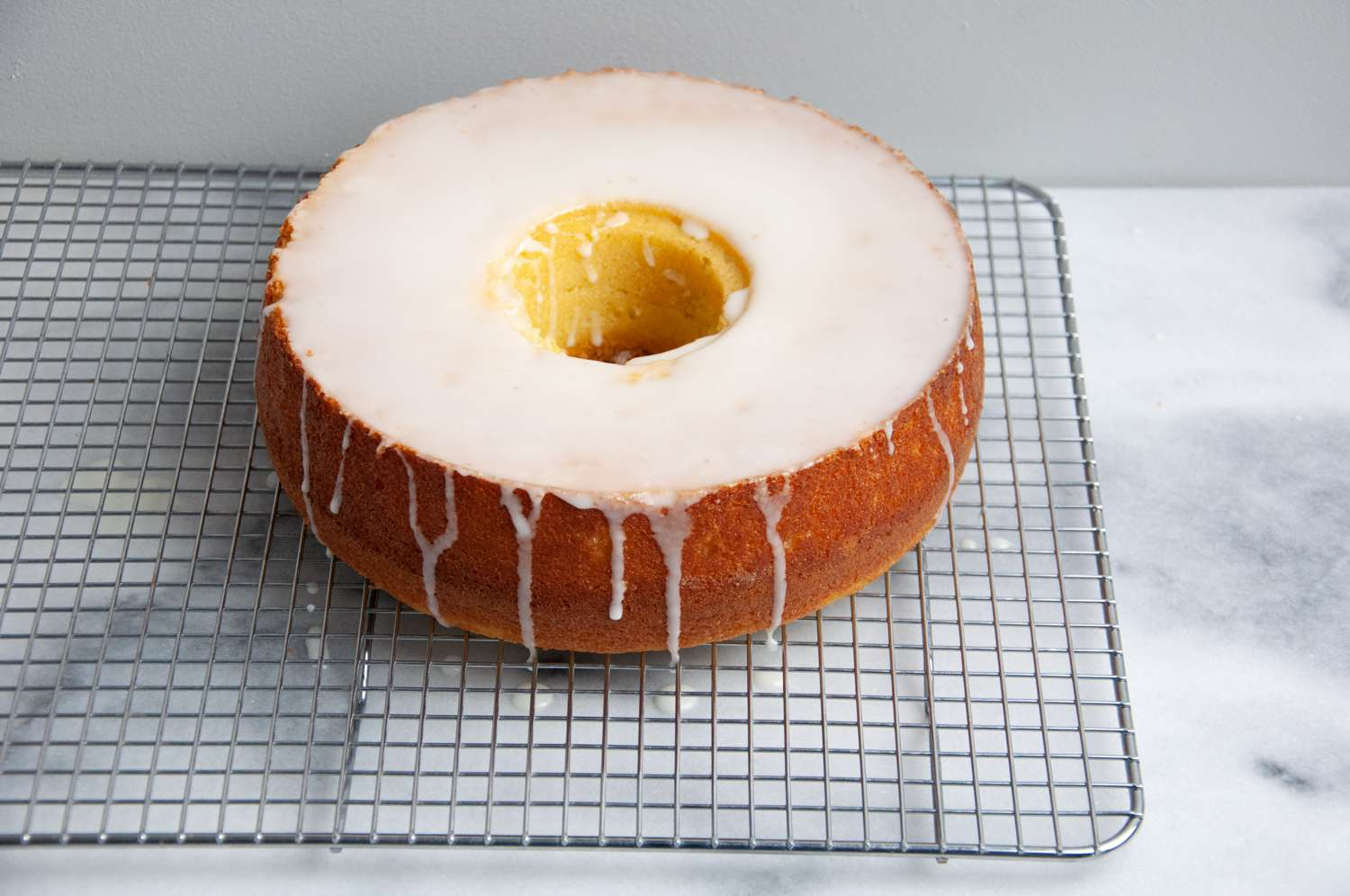 Moroccan Lemon Cake (Meskouta) with glaze on a wire cooling rack