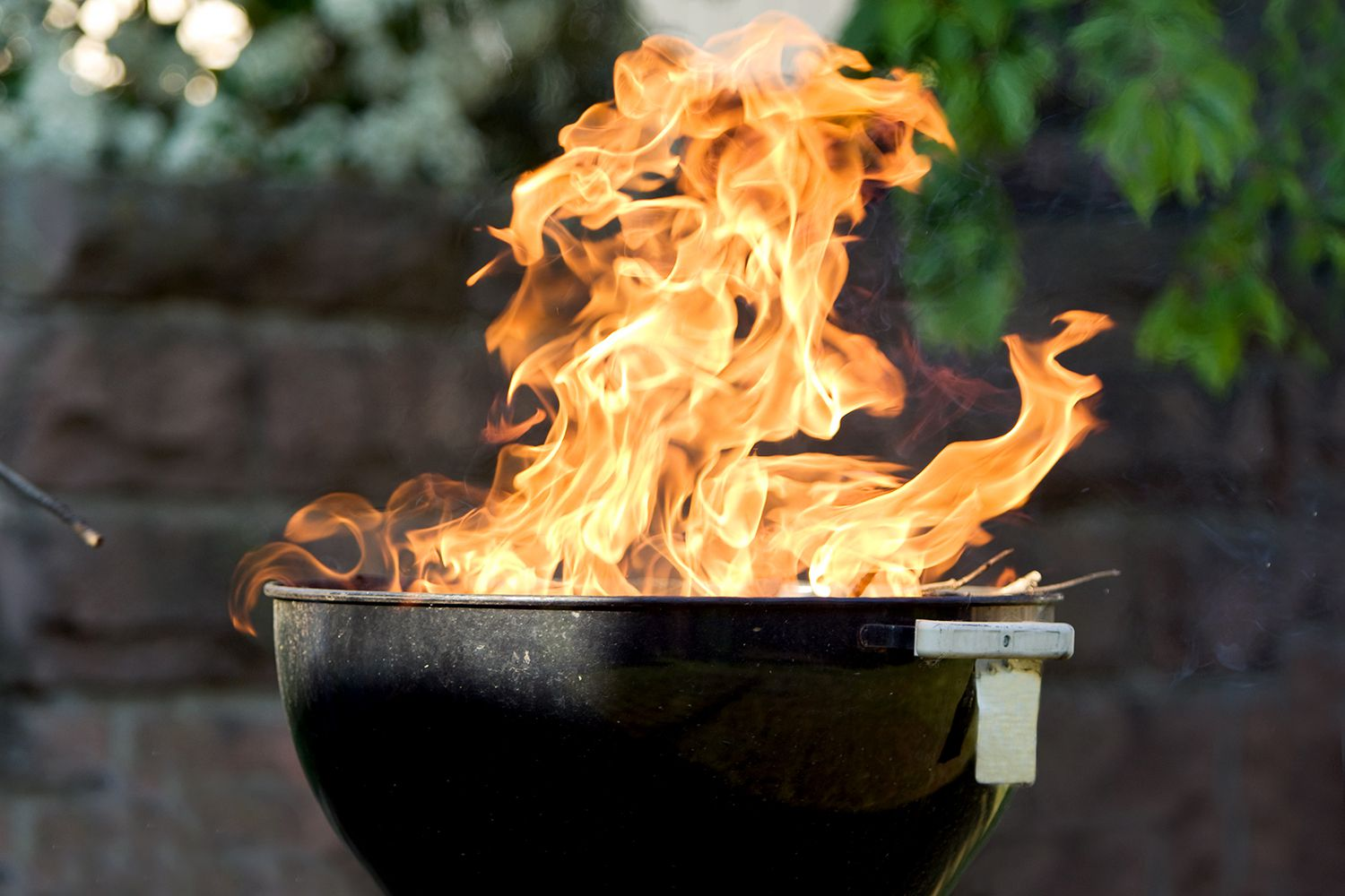 Raging flames from charcoal barbecue grill.