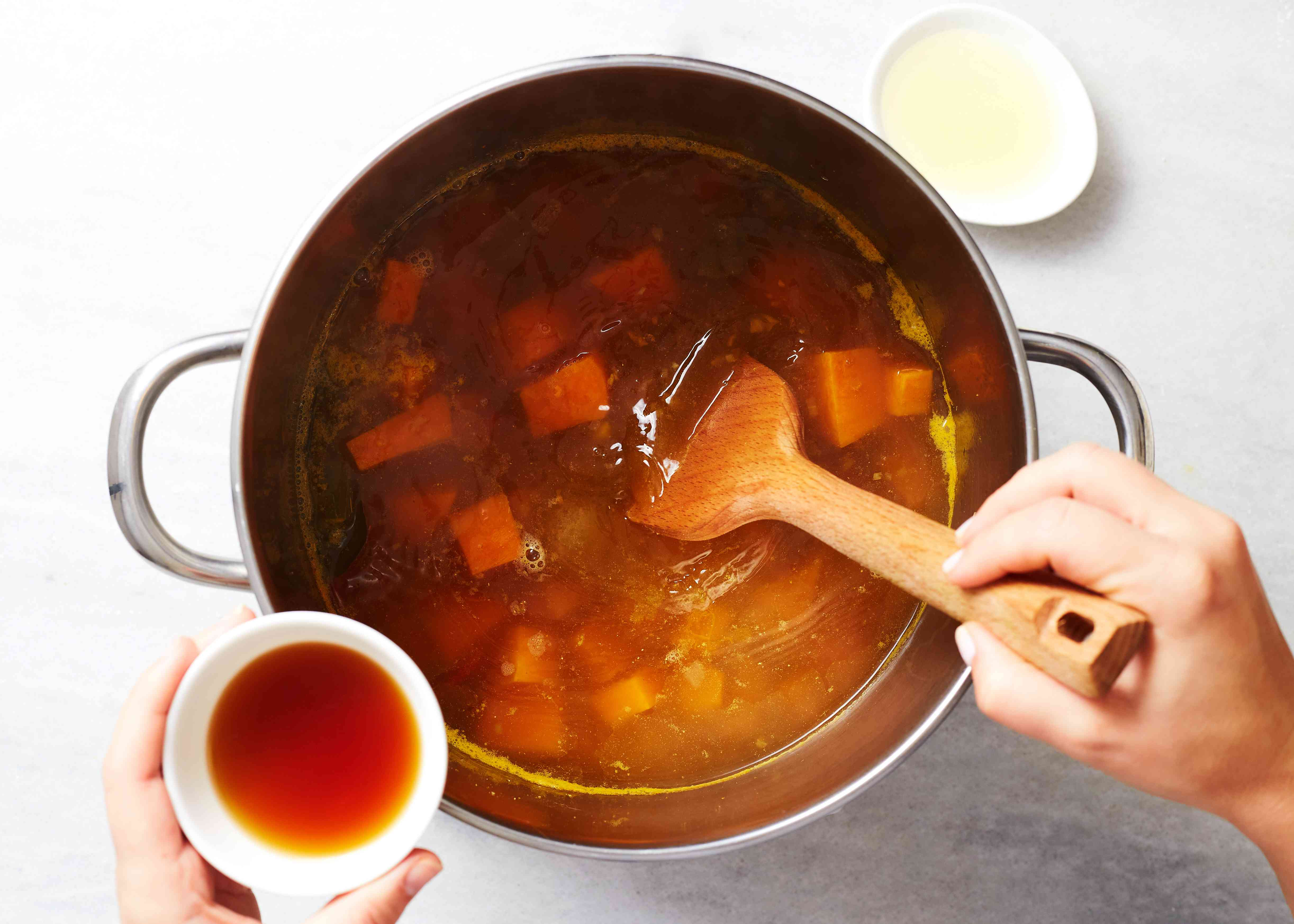 add turmeric, ground coriander and cumin, fish sauce, shrimp paste, brown sugar, and lime juice to the soup in the pot