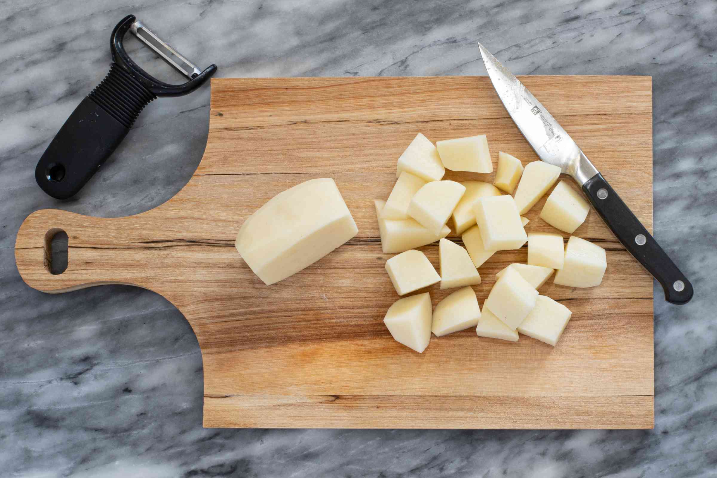 Cutting potatoes into cubes.