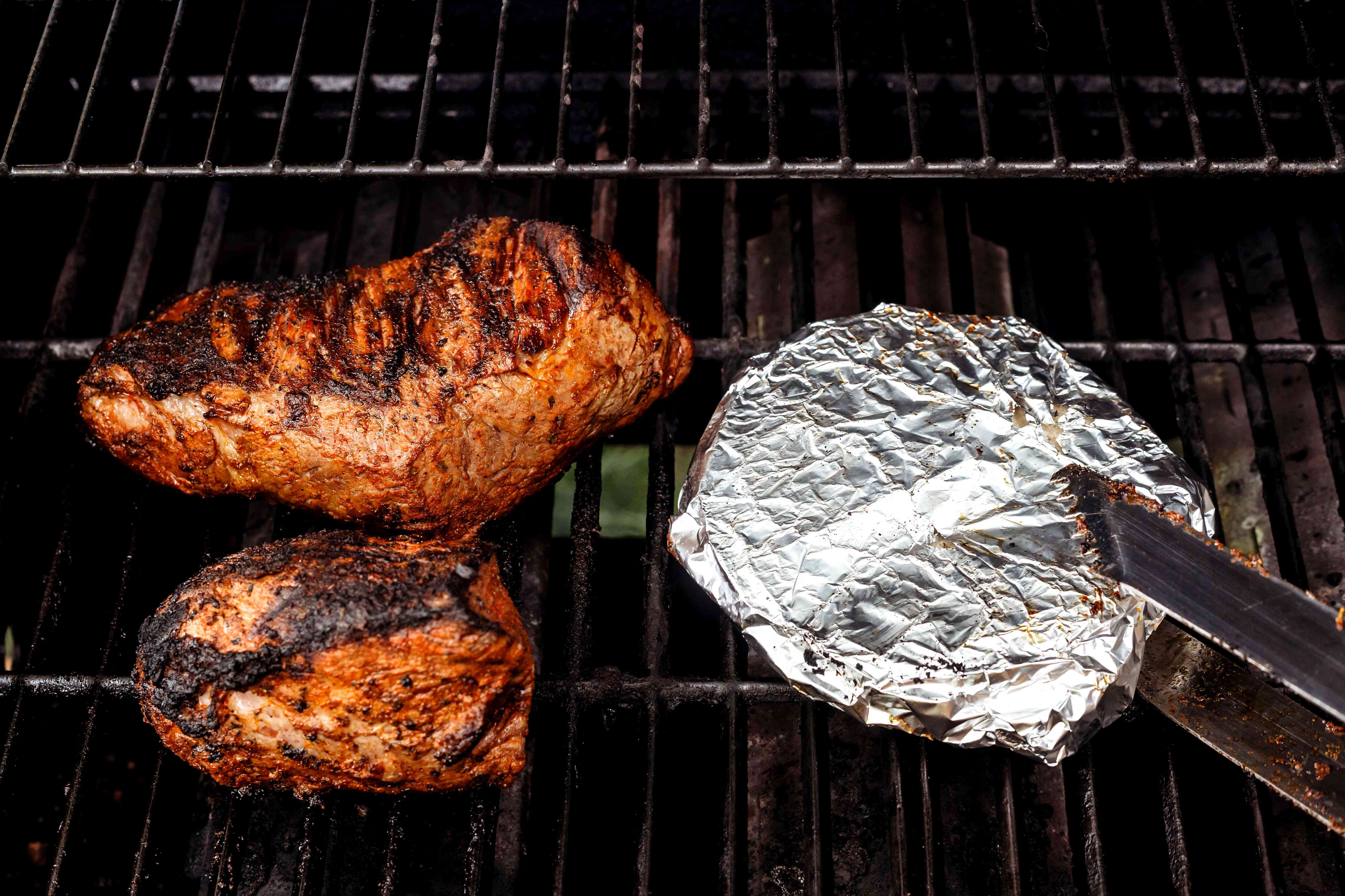 tortillas wrapped in aluminum foil and steak on the grill