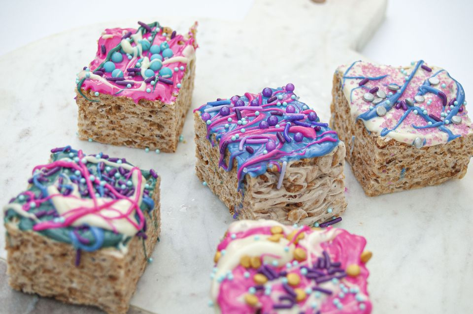 rice krispies treats coated with white chocolate and sprinkles with a blue and pink unicorn theme