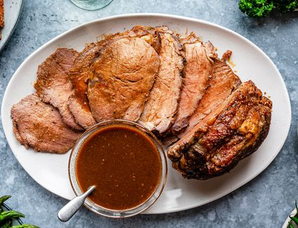 Au jus in a bowl and drizzled over beef
