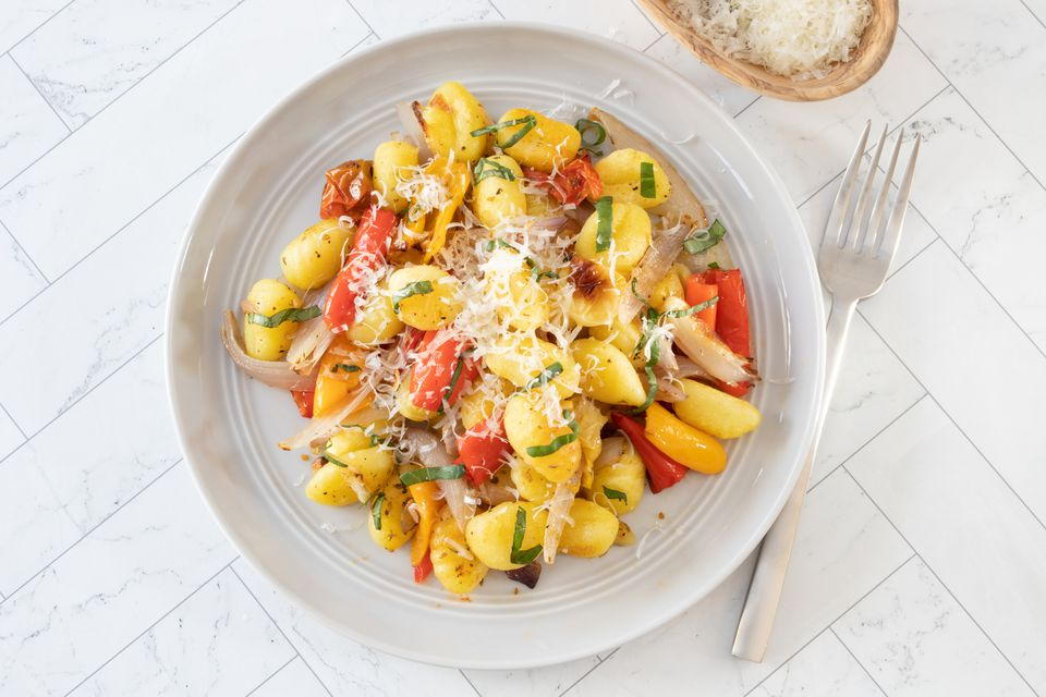 gnocchi on a plate with garnish of basil and parmesan cheese