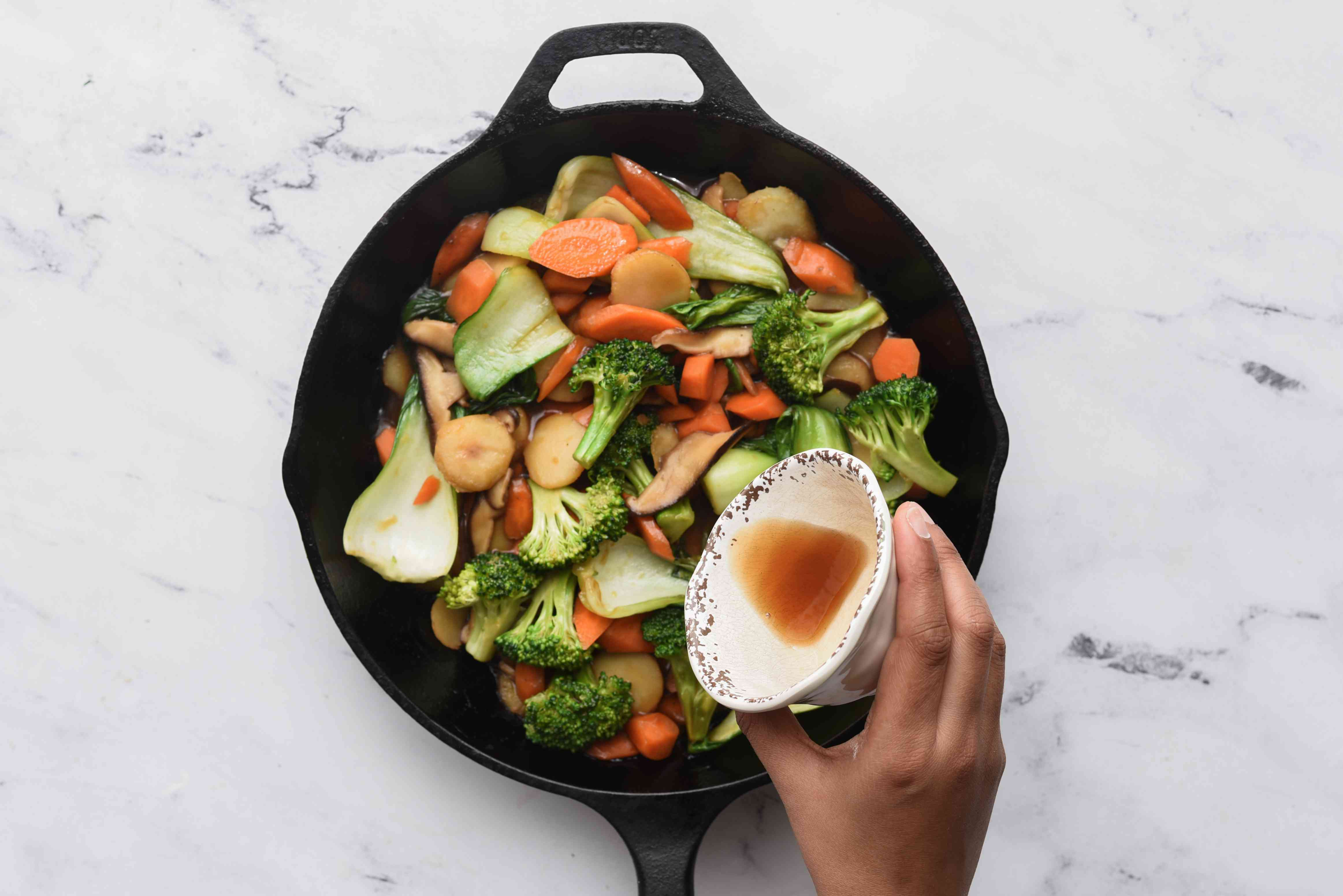 add sesame oil to the vegetables in the pan