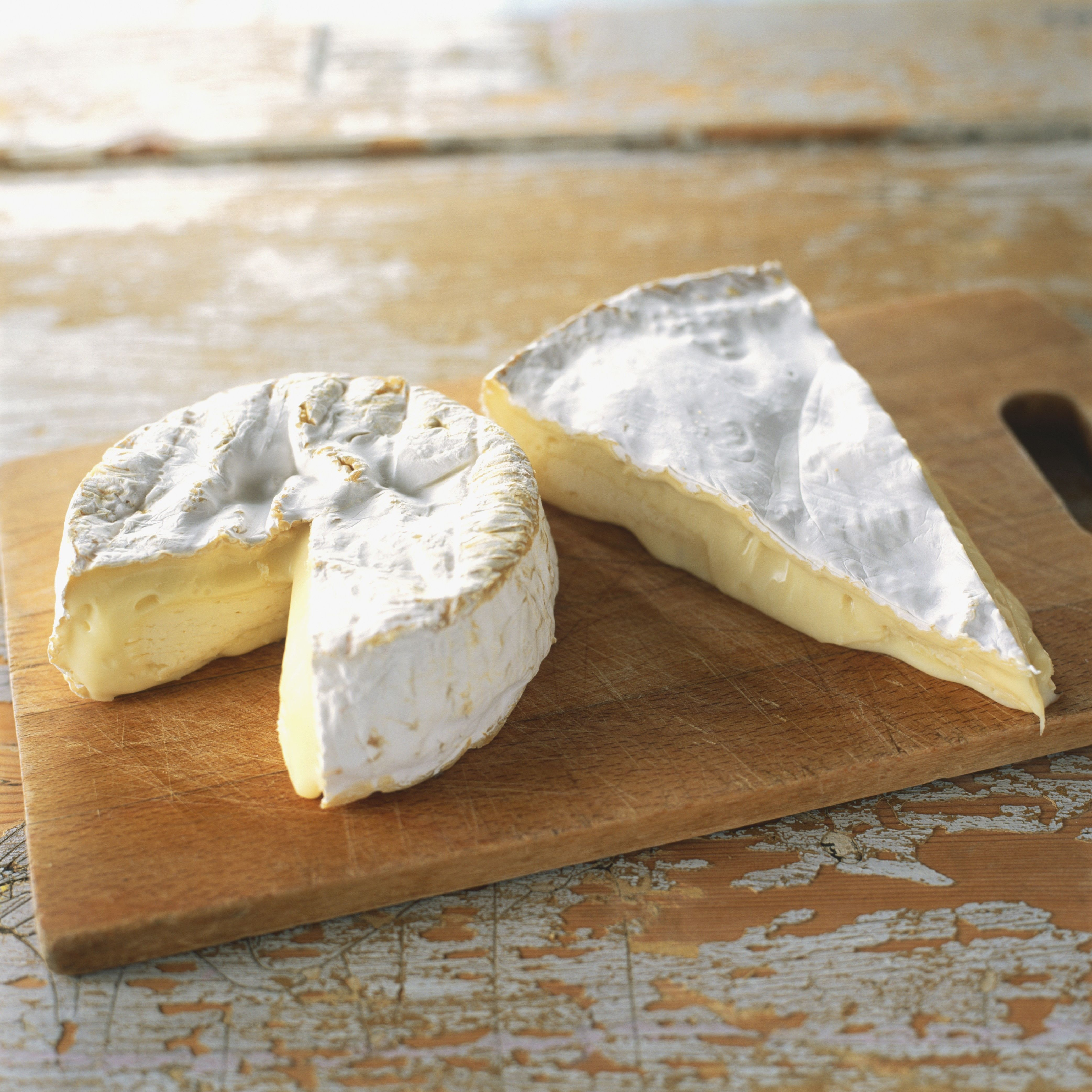 A round of Camembert cheese and slice of Brie