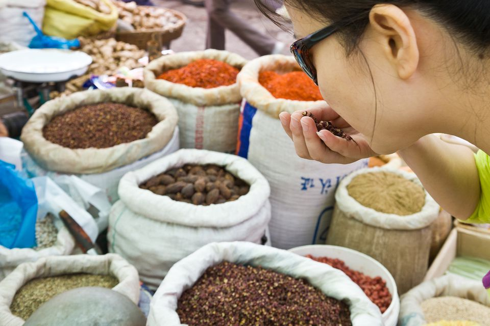 Woman smelling spices at market