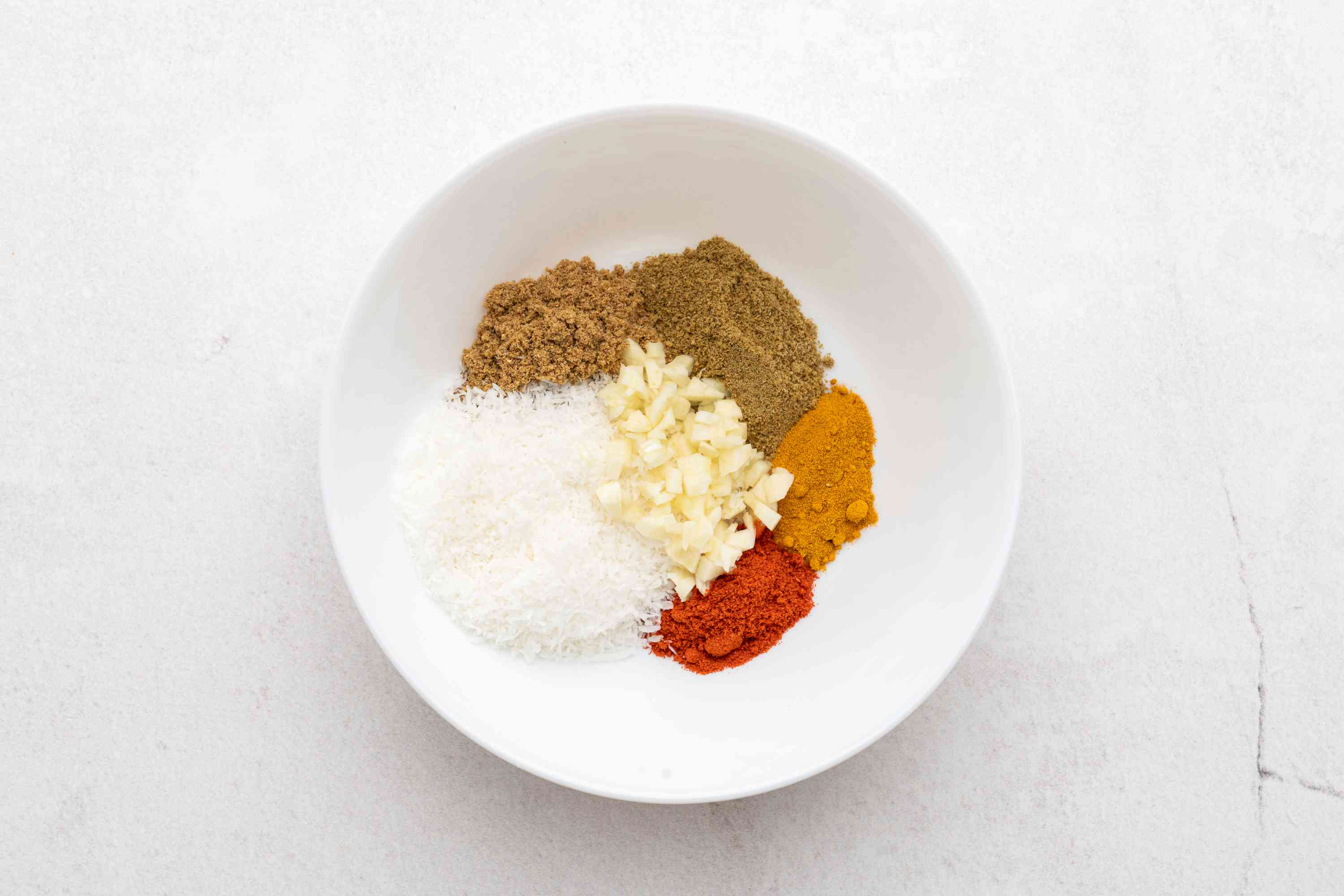 Place coriander, cumin, turmeric, red chilies, coconut and chopped garlic in a bowl