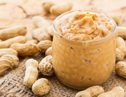 close up of peanut butter in jar surrounded by peanuts