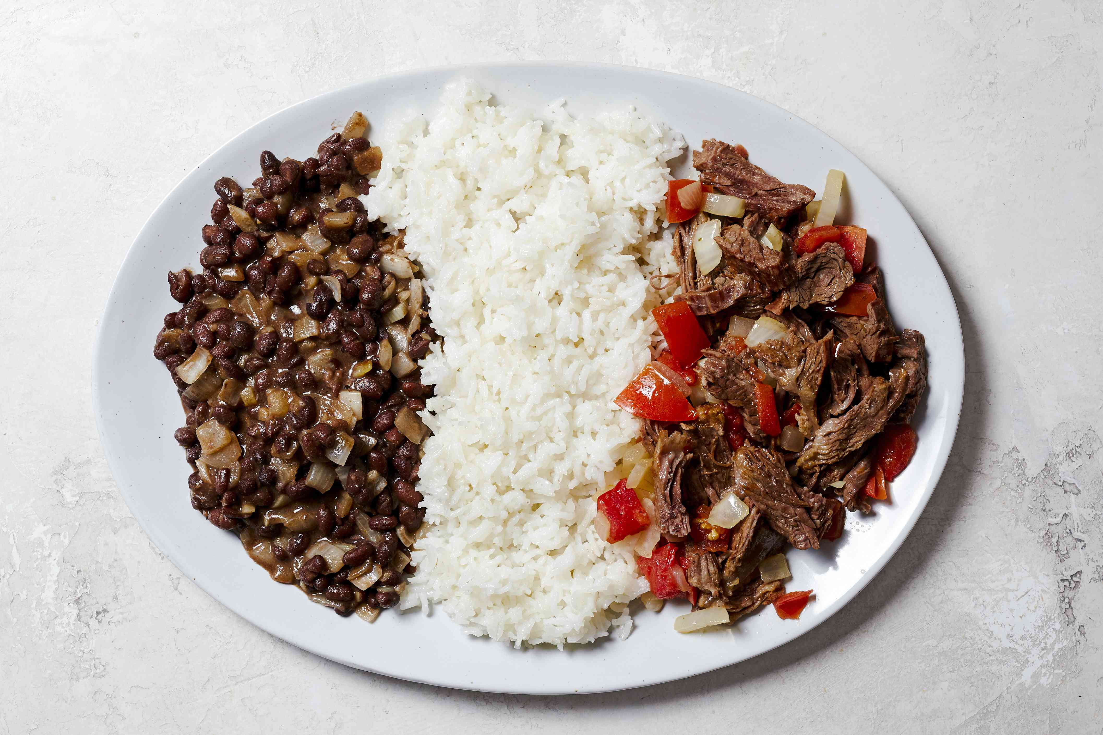 A plate with a porition of beans, rice, and steak
