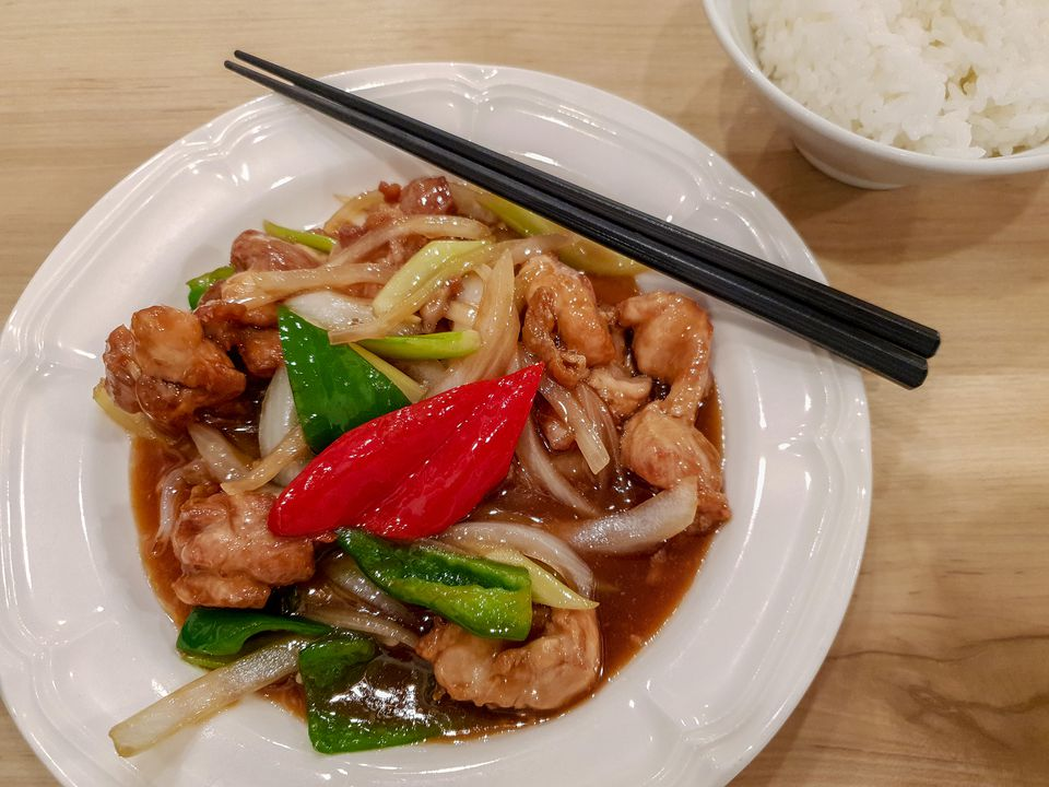 Chinese pork stir fry with vegetables on a plate with chopsticks and steamed rice in a bowl to the side.