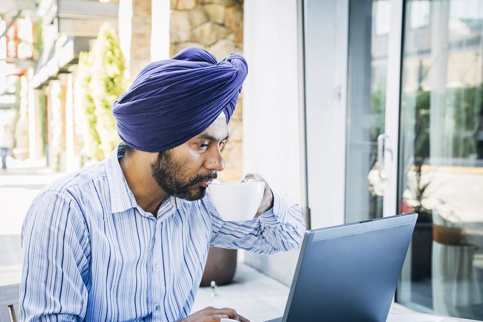 Man wearing turban using laptop at cafe