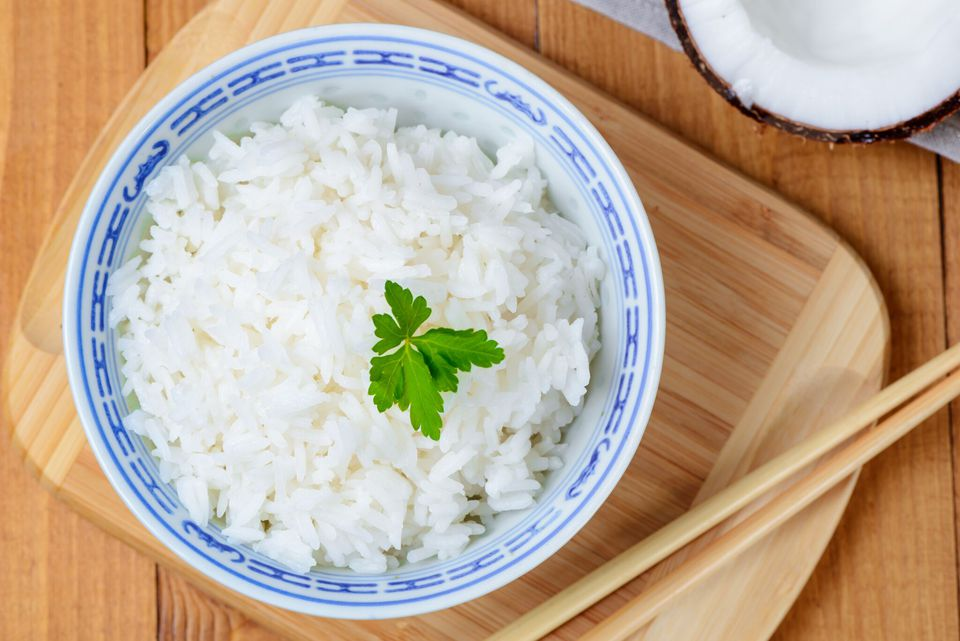 Coconut rice in a bowl with a sprig of parsley