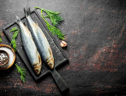 Herring on a cast iron skillet with herbs and salt