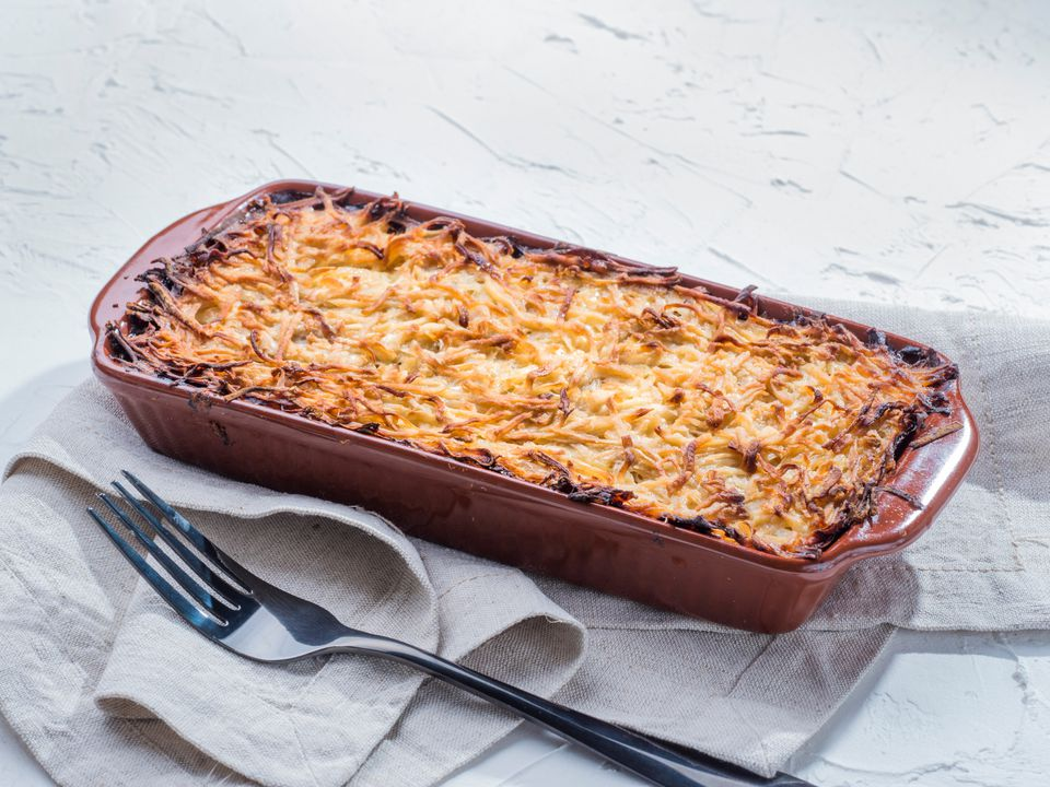 Cheese-topped casserole against white background