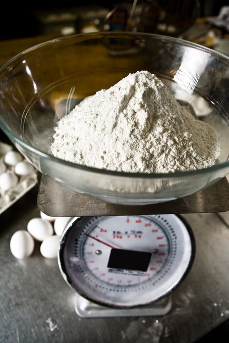 Bowl of flour on scale in kitchen with eggs