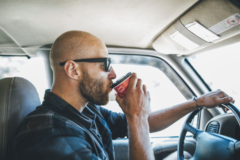 man drinking coffee while driving